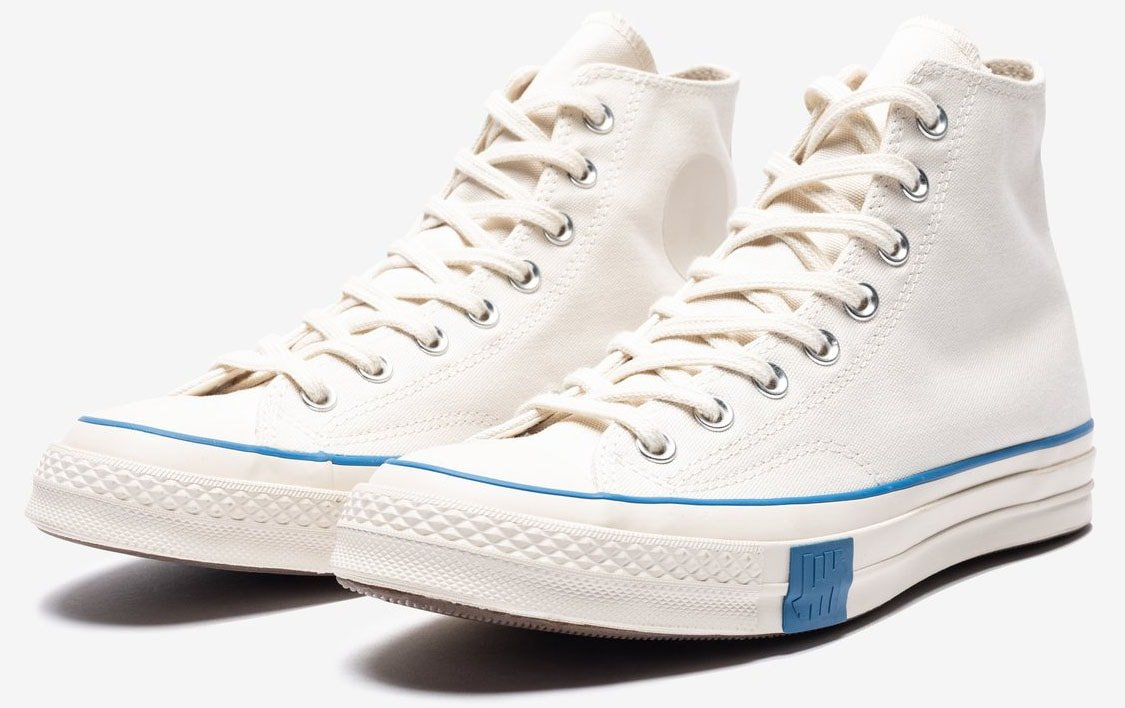 A minimalist pair of Converse Chucks with blue trims and Undefeated branding