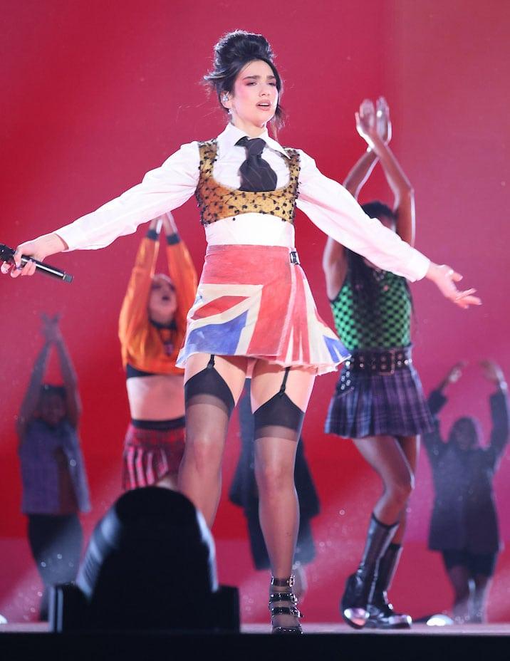 Dua Lipa wears custom Vivienne Westwood Union Jack mini skirt with white shirt and gold corset