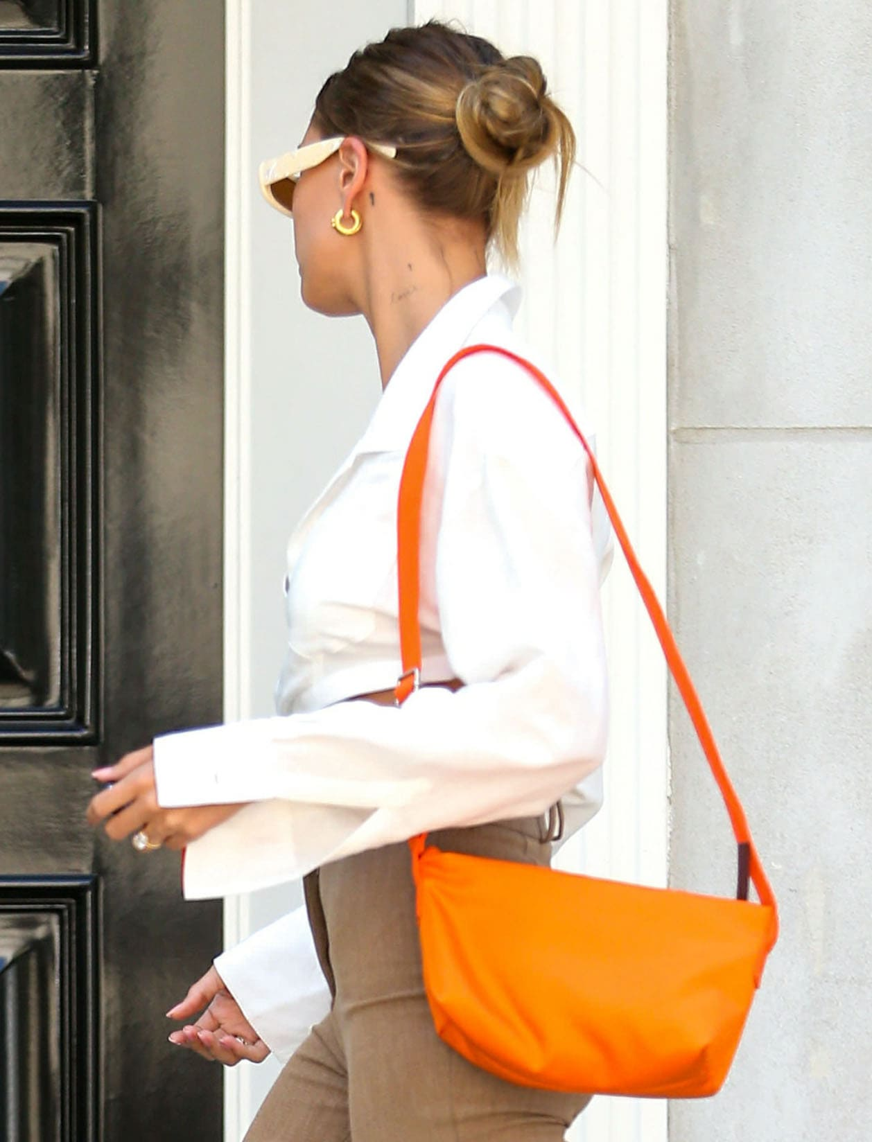 Hailey Bieber gave her neutral outfit a pop of color with bright orange The Attico Trousse bag
