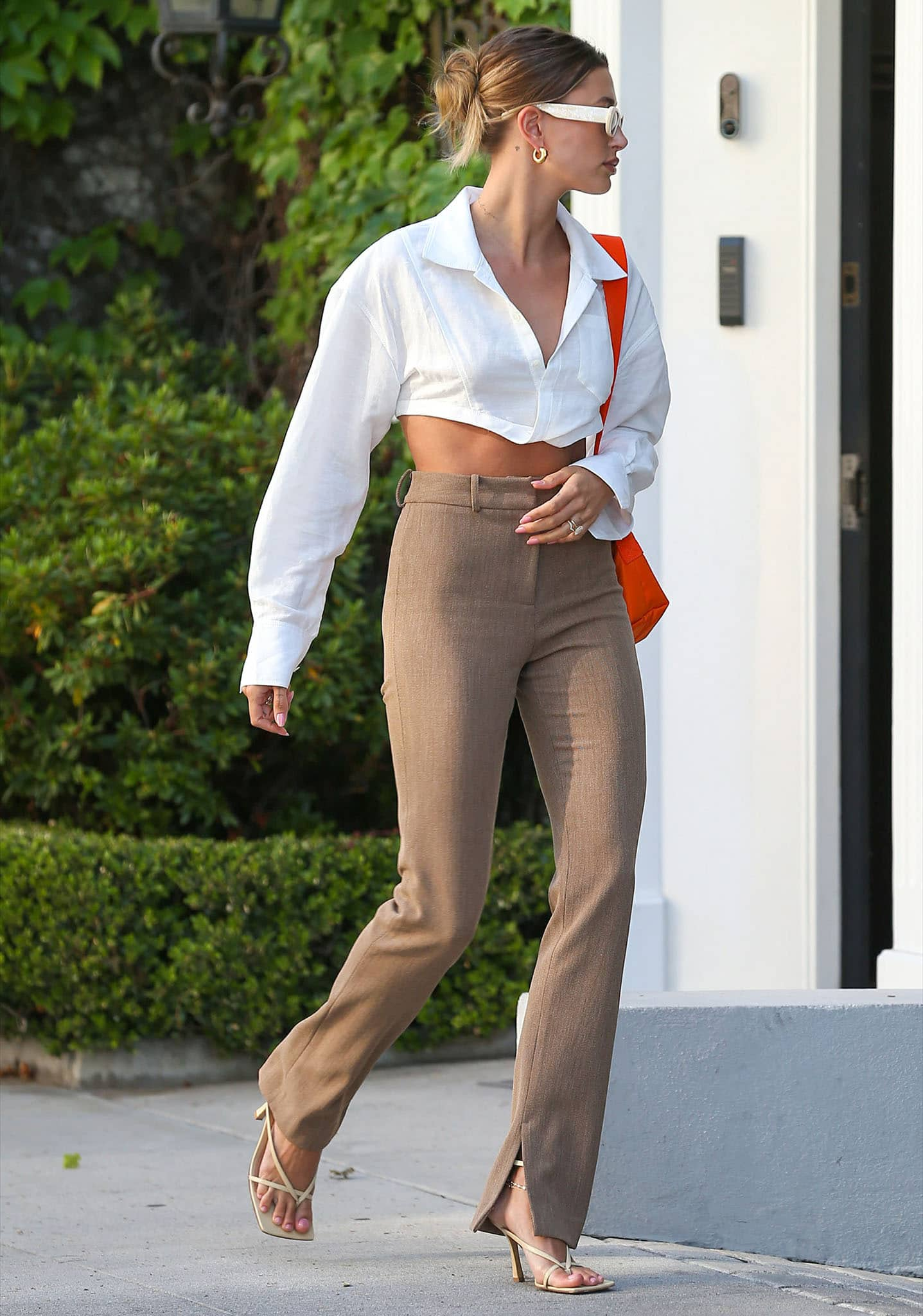Hailey Bieber puts a sexy twist on business chic in Jacquemus crop white shirt and Musier high-waist trousers