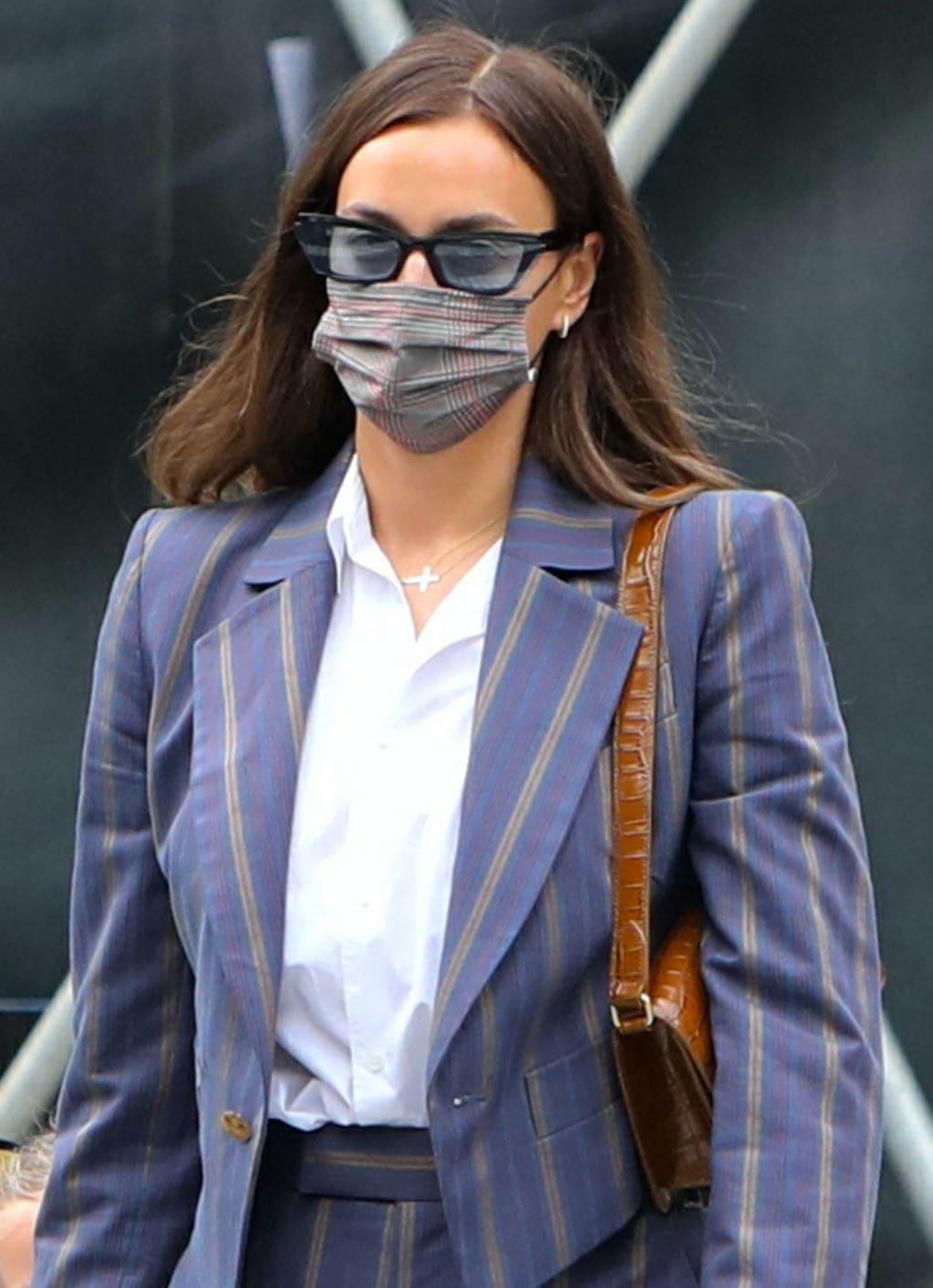 Irina Shayk hides her face in Fenty Inside Story sunnies and Maskc tartan face mask