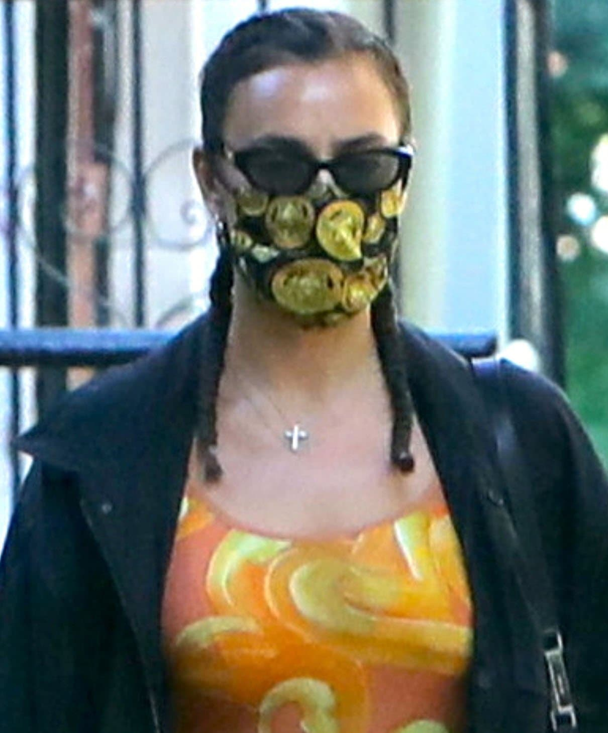 Irina Shayk wears cornrows with braided pigtails and hides her face underneath her Poppy Lissiman sunnies and Versace face mask