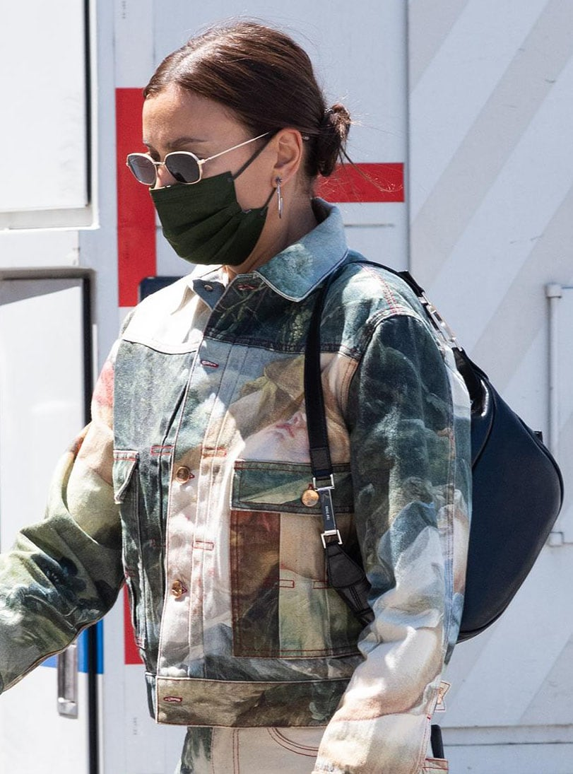 Irina Shayk wears a low bun and hides her eyes behind a pair of Illesteva East Houston sunnies