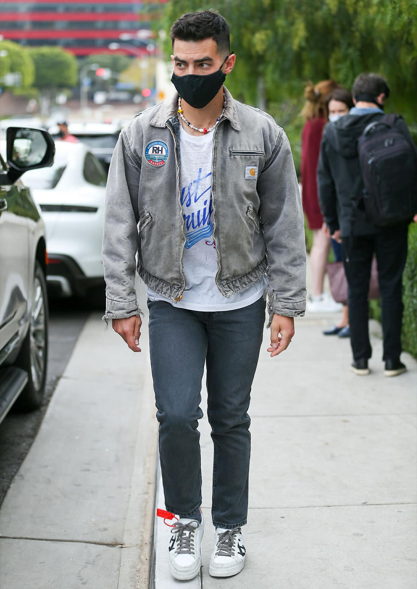 Joe Jonas keeps a casual look with a white graphic tee, a gray denim jacket, denim jeans, and Off-White shoes