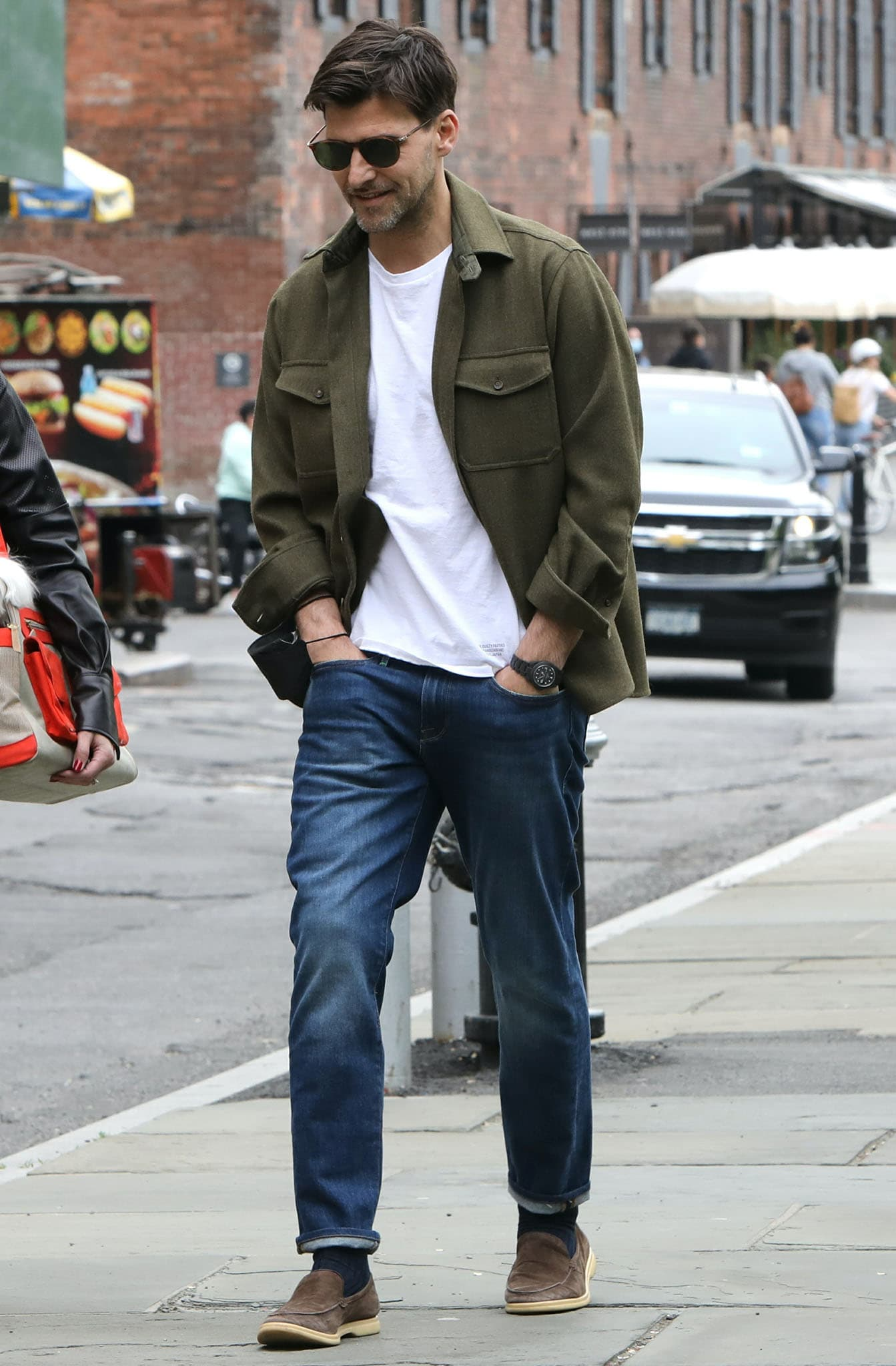 Johannes Huebl looks dapper in a white tee with blue jeans and an army green jacket