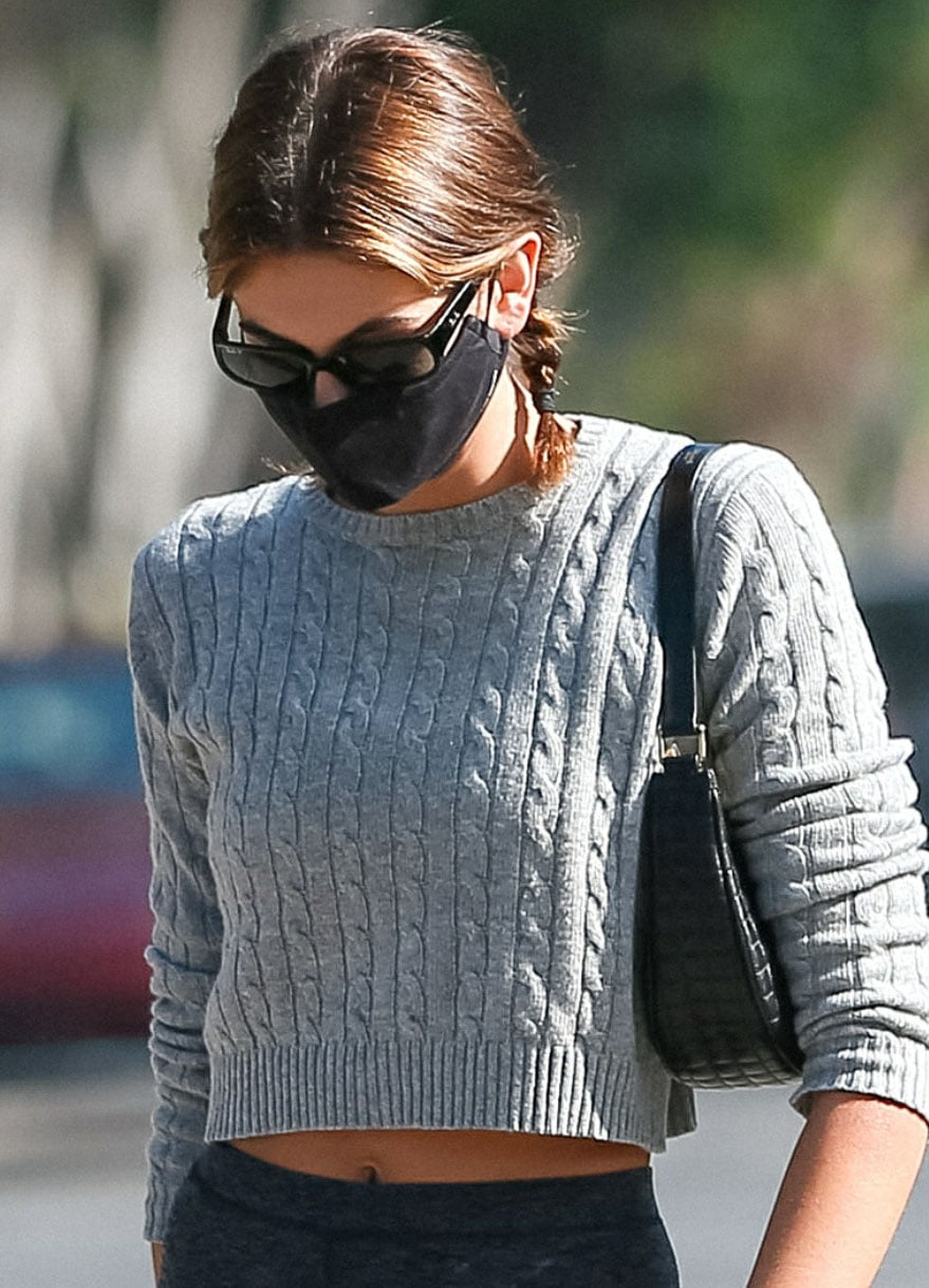 Kaia Gerber wears cute pigtail braids and covers her face with RayBan sunglasses and a face mask