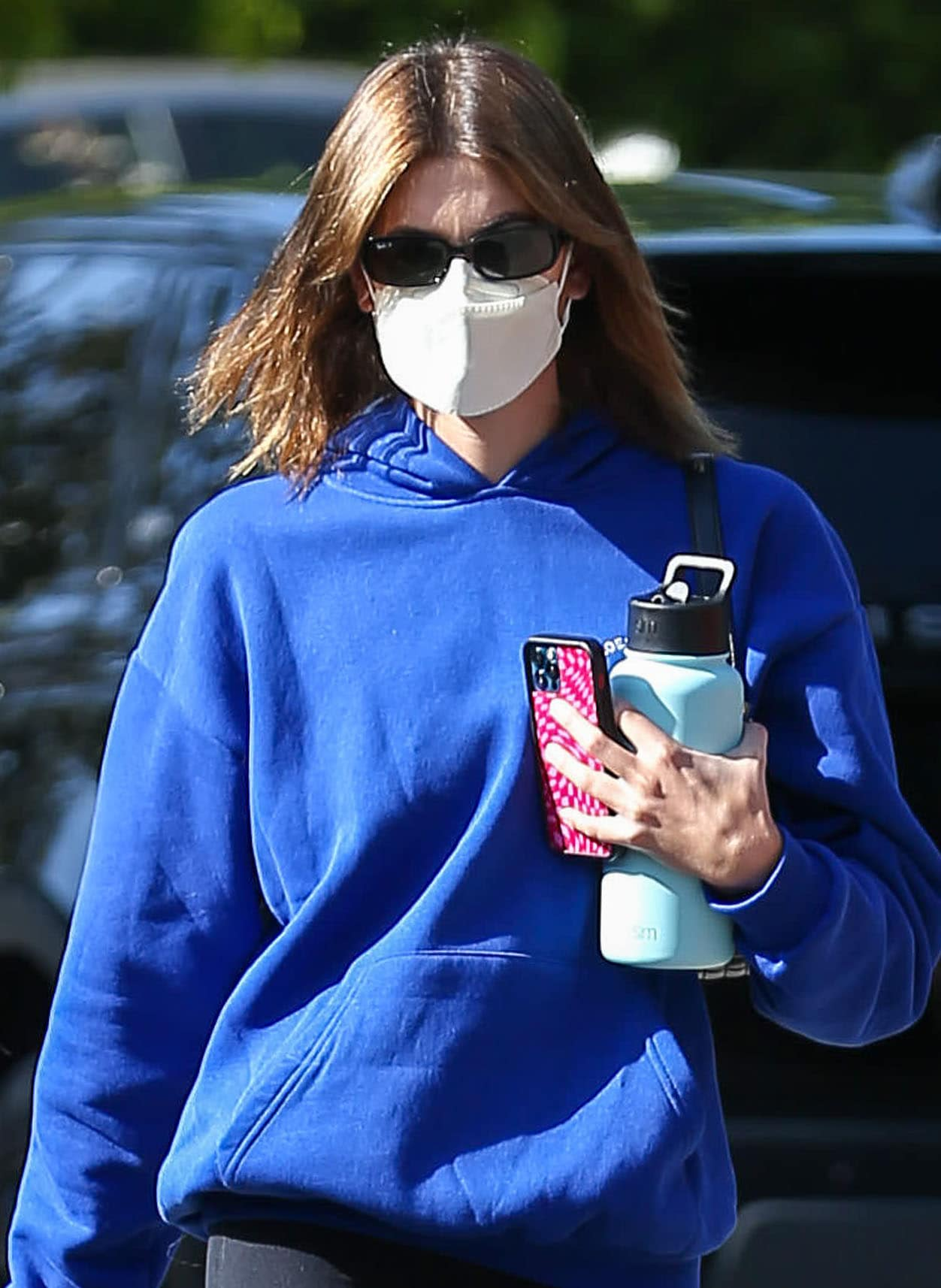 Kaia Gerber keeps a low profile with Ray-Ban sunglasses and Kaze Champagne face mask