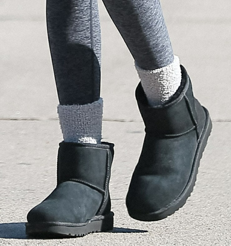 Kaia Gerber wears fuzzy gray socks with UGG Ultra Mini Classic boots