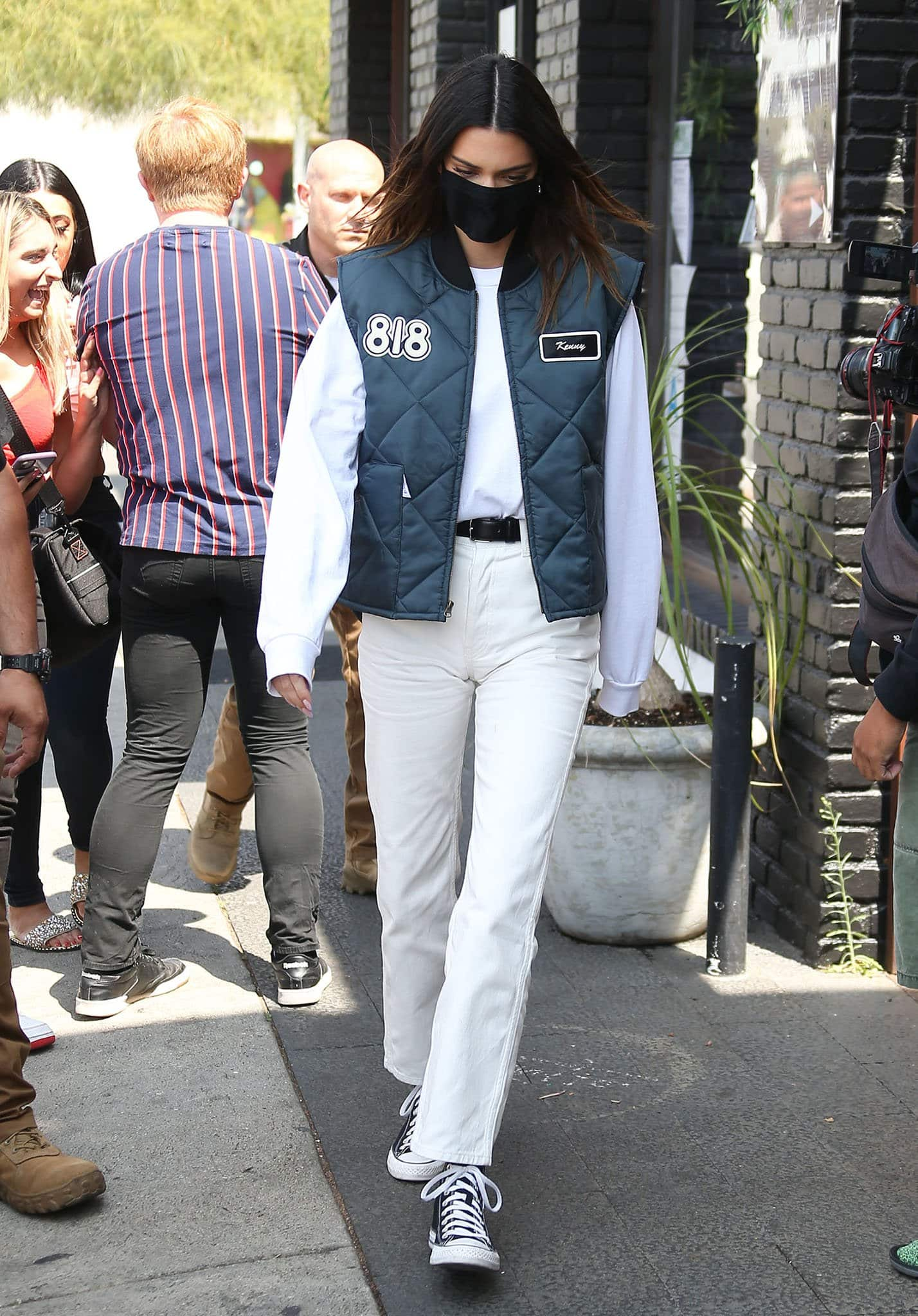 Kendall Jenner goes for a delivery driver look in 818-tagged vest with a white sweater and a pair of Style Addict pants