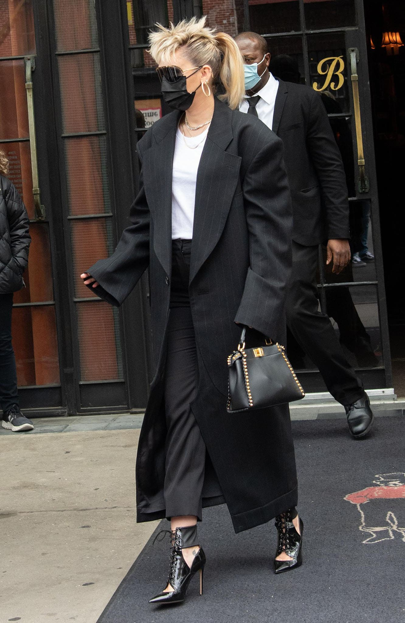 Miley Cyrus wears Junya Watanabe pinstriped long coat over a white tee and black pants combo