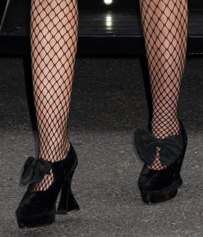 Miley Cyrus wears fishnets with her black velvety bow-detailed heels