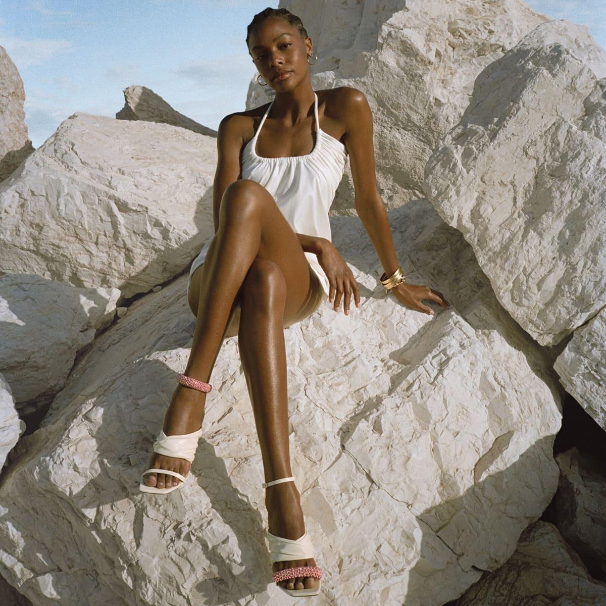 Model wearing Jimmy Choo's Ocean 90 summer sandals featuring a pink bracelet