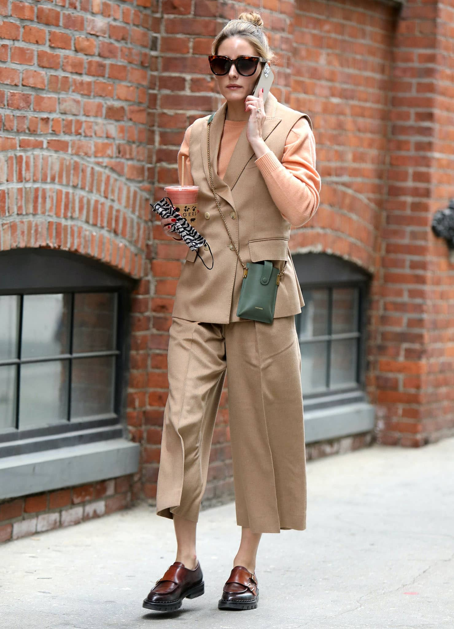 Olivia Palermo grabs smoothie in Max Mara camel trousers, vest, and sweater in New York City on May 3, 2021