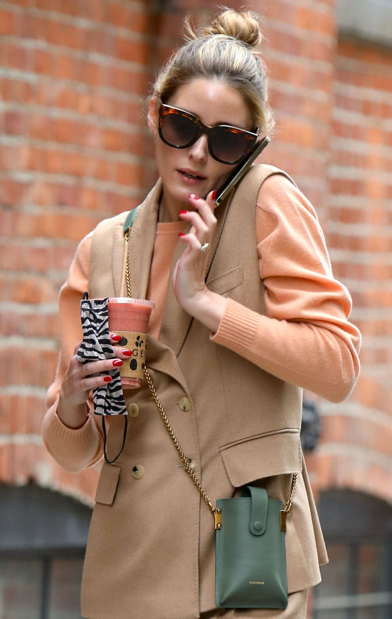 Carrying an olive green Pipatchara Pandemic Relief bag, Olivia Palermo looks chic with her high bun and tortoiseshell sunglasses
