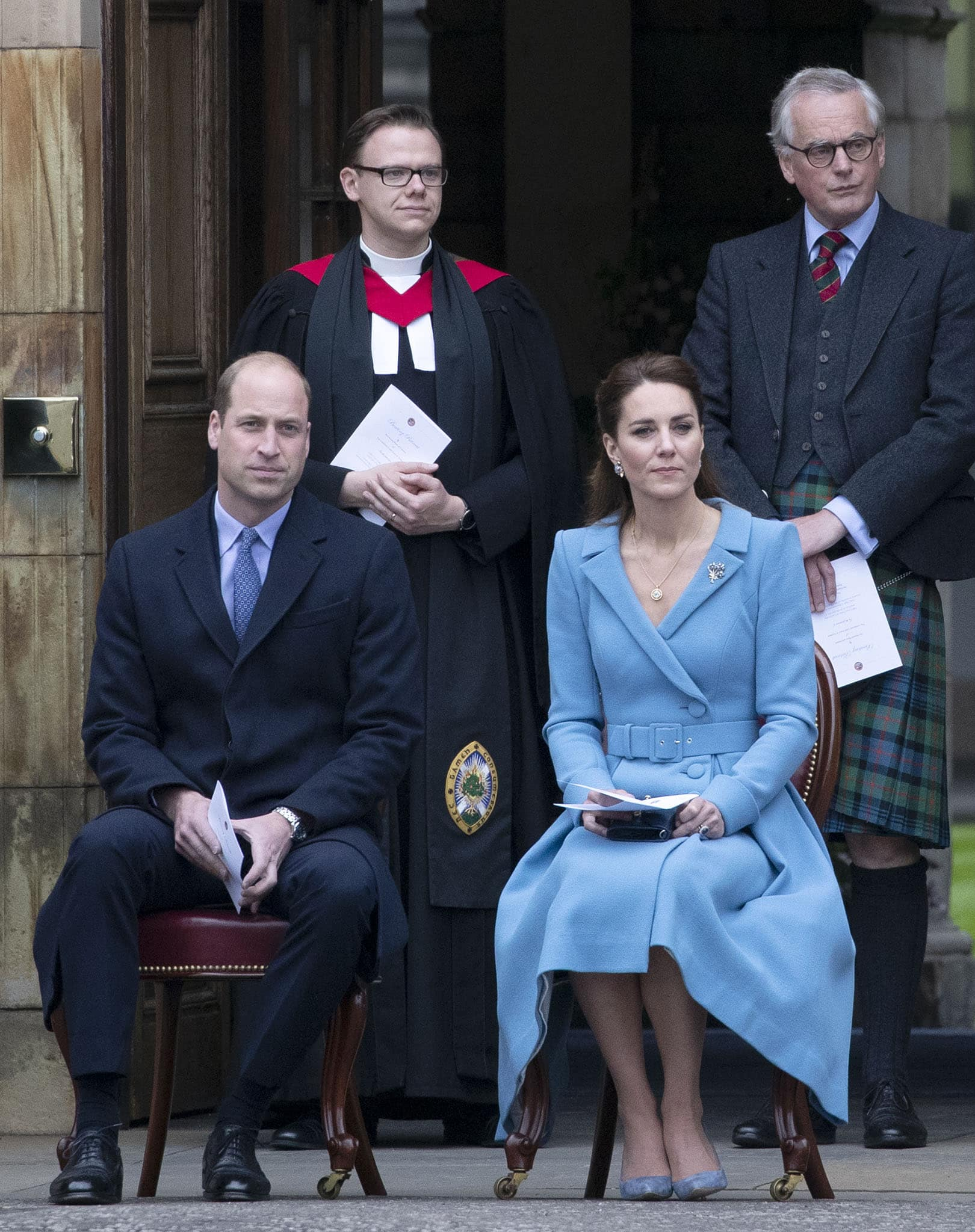 Prince William wears a navy blue suit with a printed necktie, while Kate Middleton opts for a light blue dress