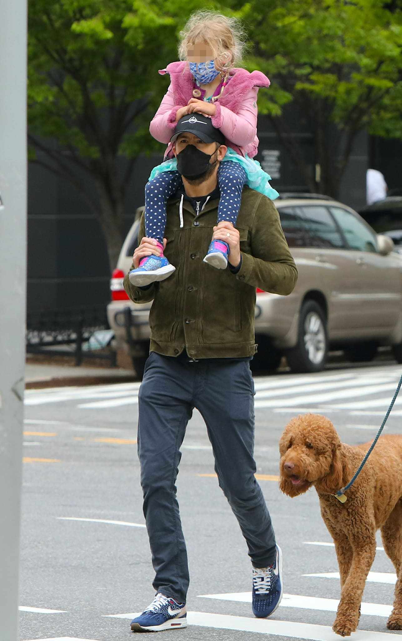 Ryan Reynolds carries his daughter on his shoulders in green jacket, navy pants, and Nike shoes