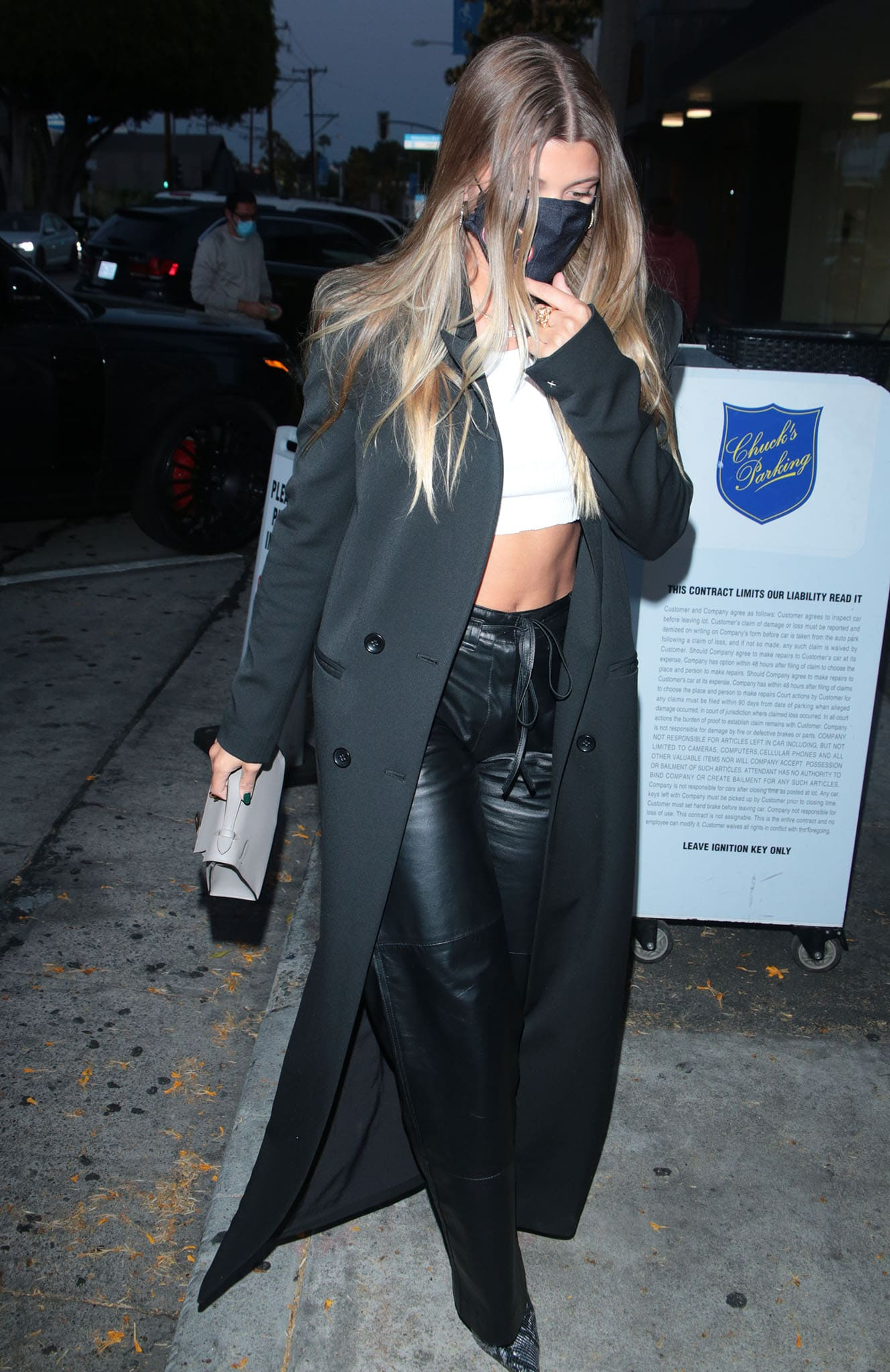 Sofia Richie displays her toned abs in a crop top, leather pants, and The Row wool coat