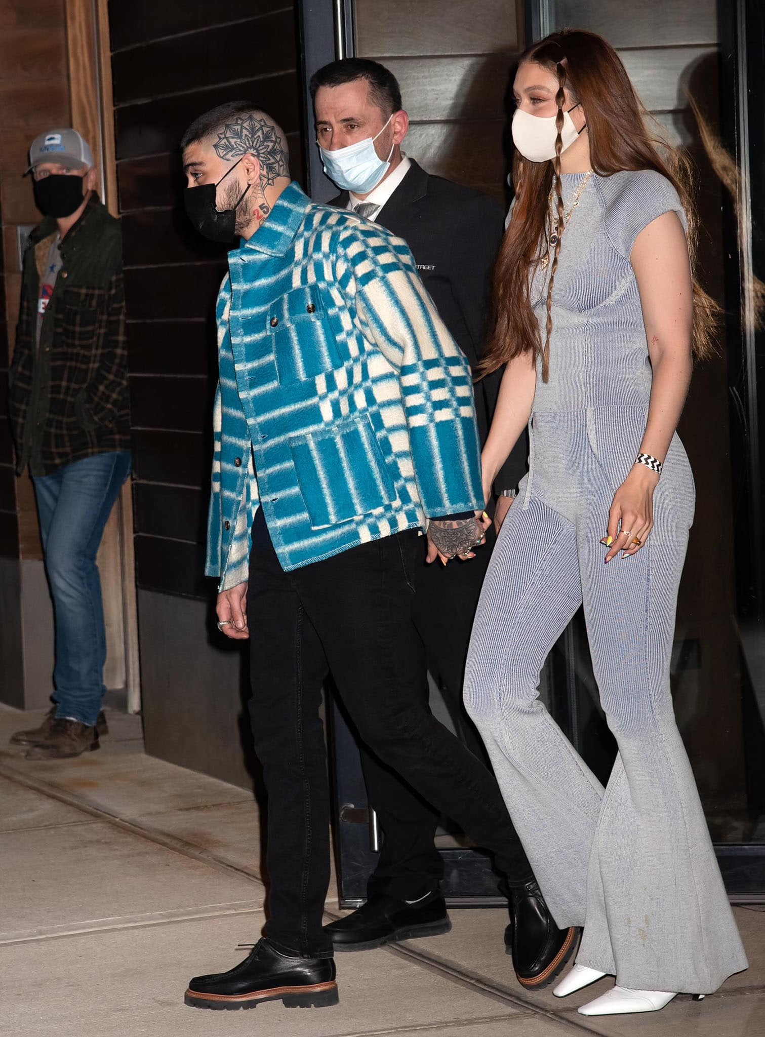 Zayn Malik holds hands with Gigi Hadid in a plaid shirt with black pants and oxford shoes