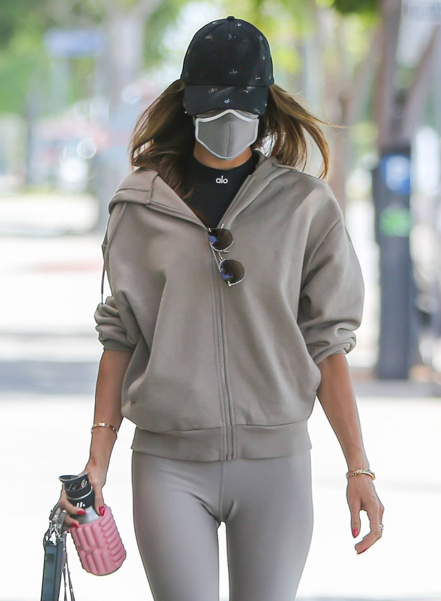 Alessandra Ambrosio styles her workout outfit with Alo Yoga cap, a hoodie, and a face mask