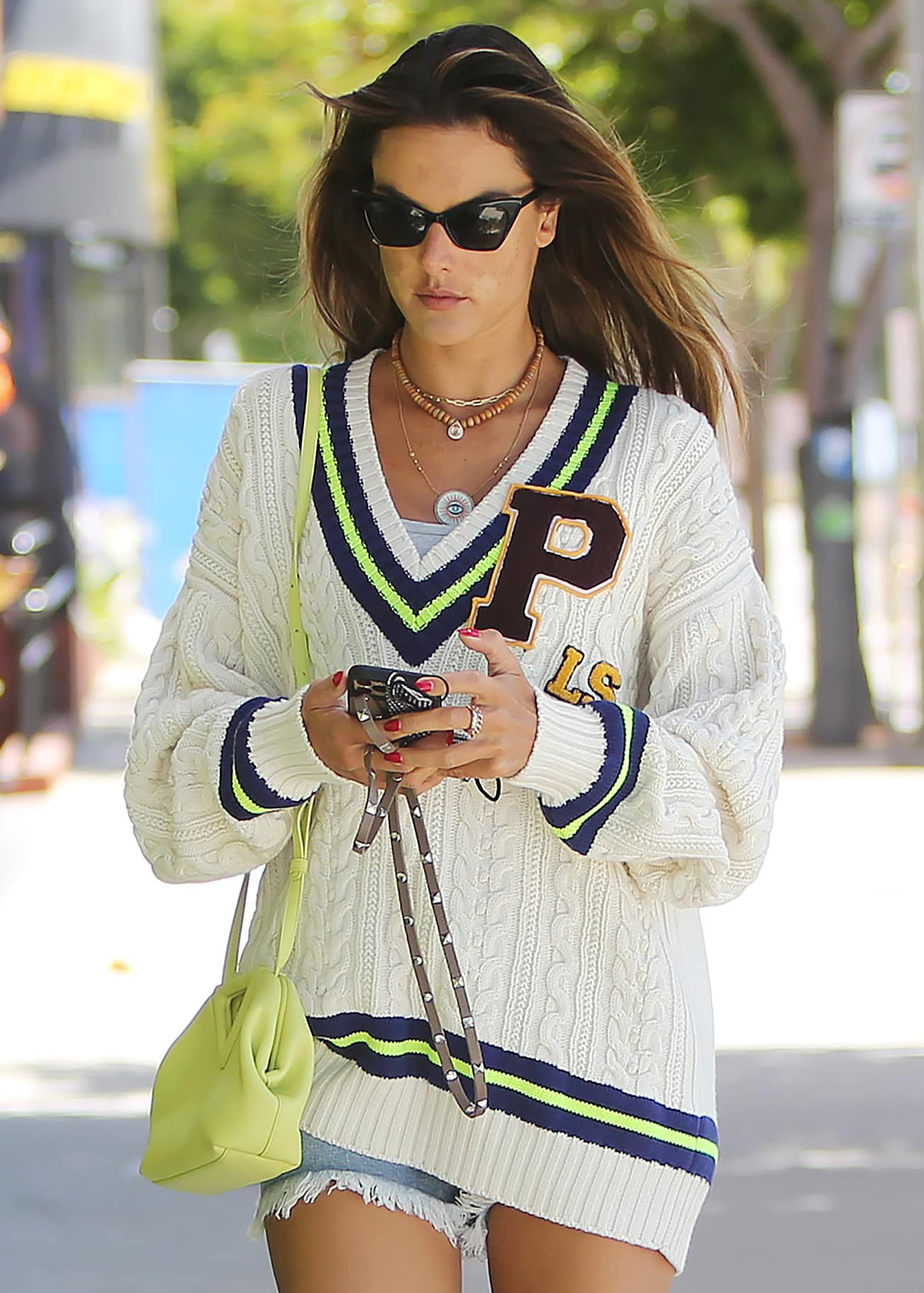 Alessandra Ambrosio styles her casual look with Jacquie Aiche necklaces, cat-eye sunnies, and a Bottega Veneta bag