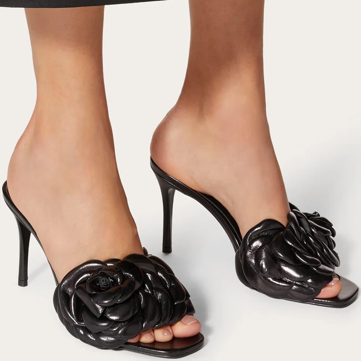Valentino Garavani's black Atelier 03 rose edition sandals with leather petals creating a 3D rose detail