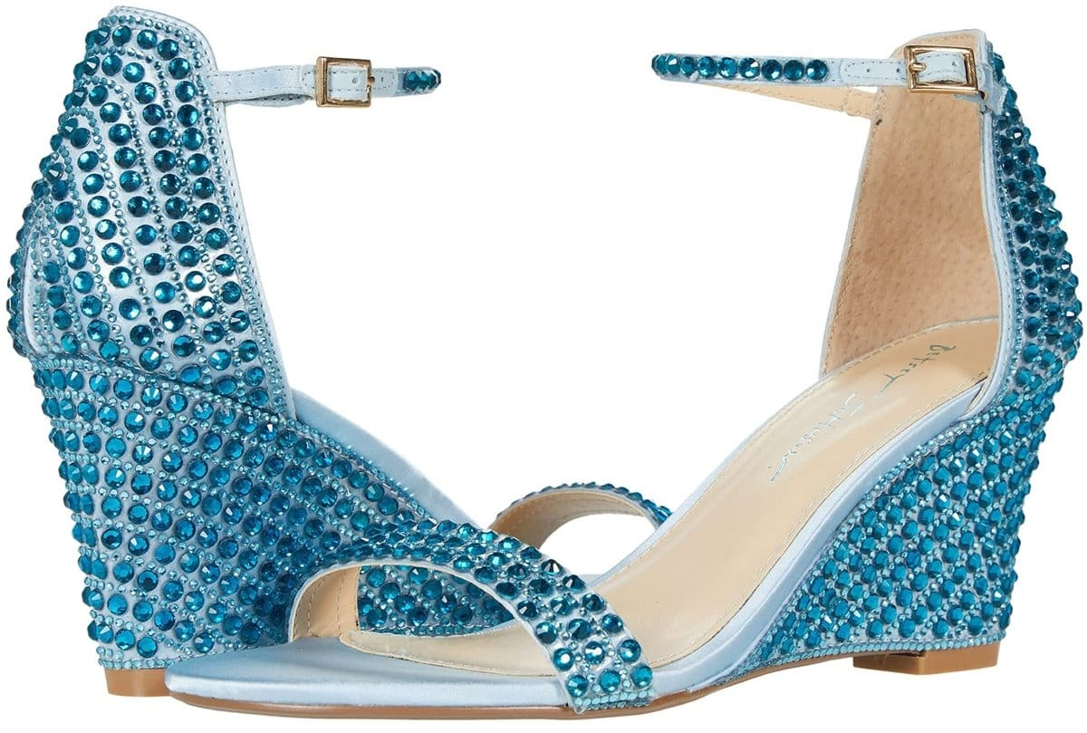Elevated with a wedge heel, Betsey Johnson's light blue Debbie wedge sandal is embellished with rhinestones to boost your ensemble