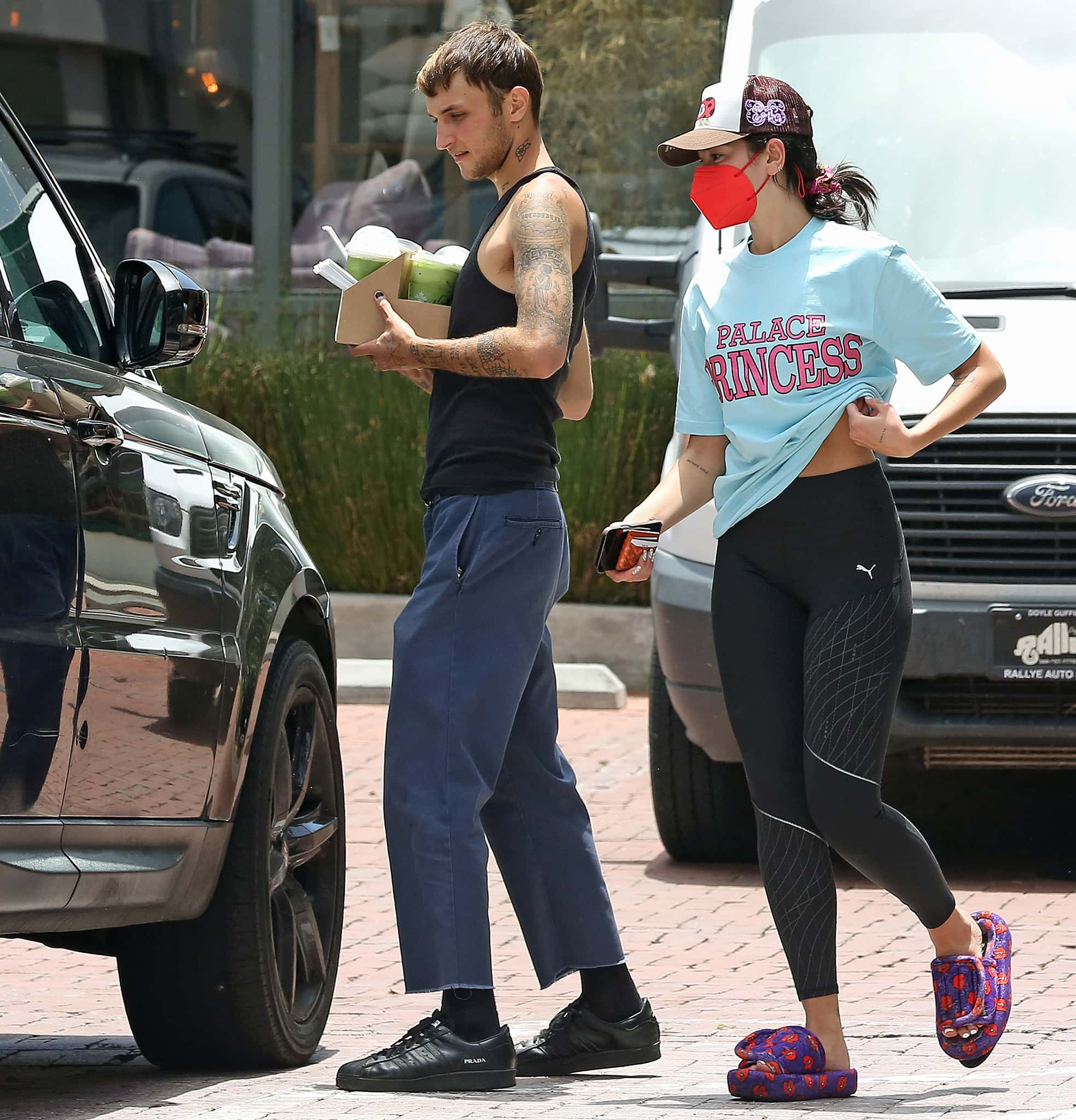 Anwar Hadid shows off his tattoos in a black tank top paired with loose pants and Prada sneakers