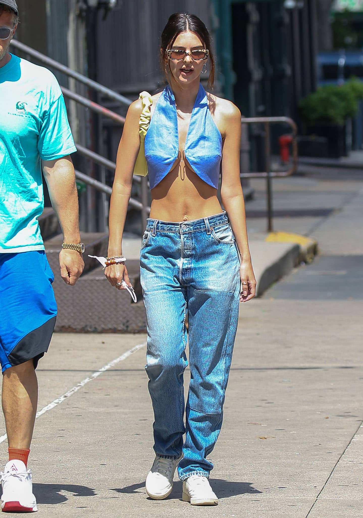 Emily Ratajkowski flashes abs and underboob in blue halterneck crop top and low-rise jeans