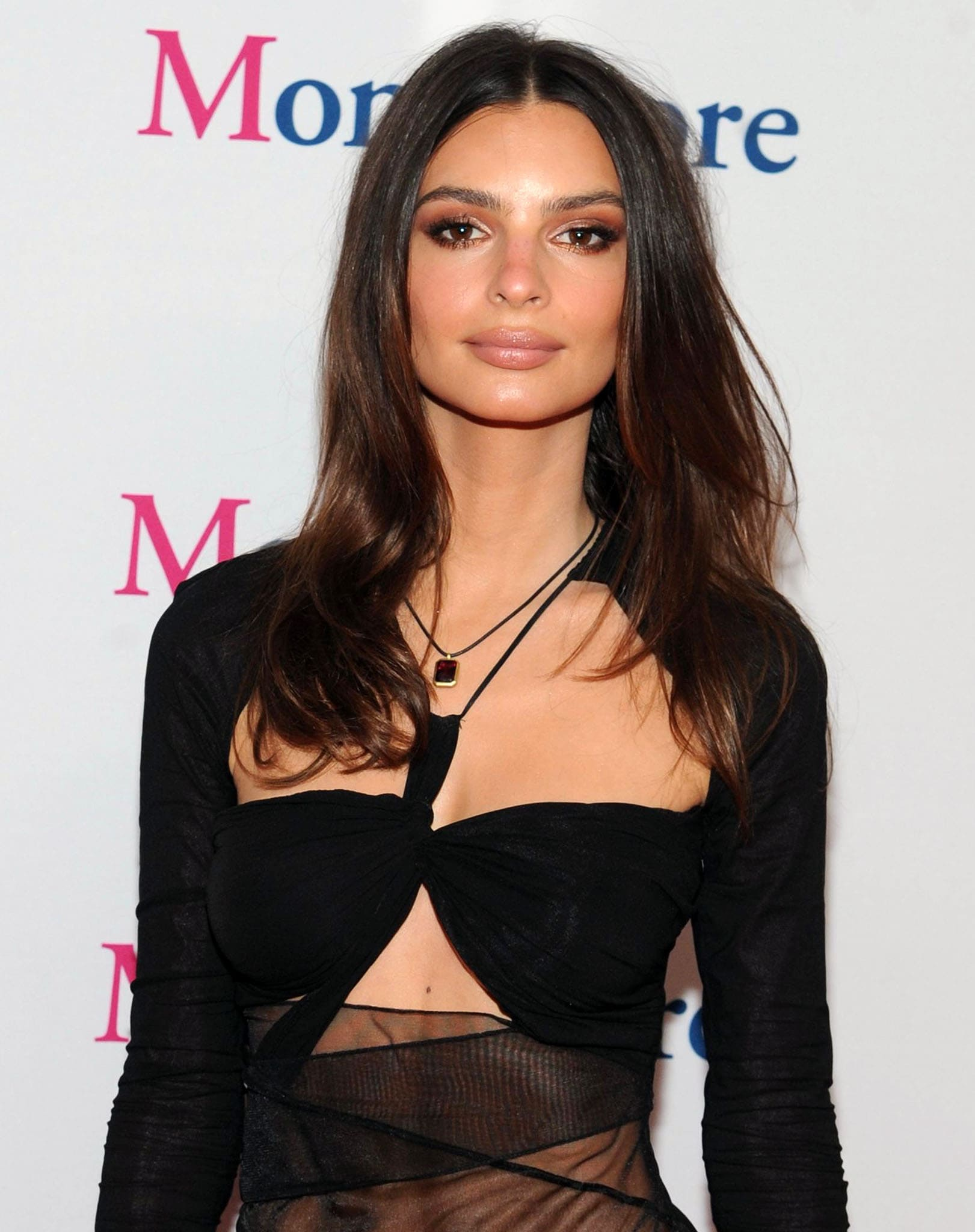 Emily Ratajkowski creates a sultry look with her blown-out hair, subtle red smokey eyeshadow, and nude lipstick