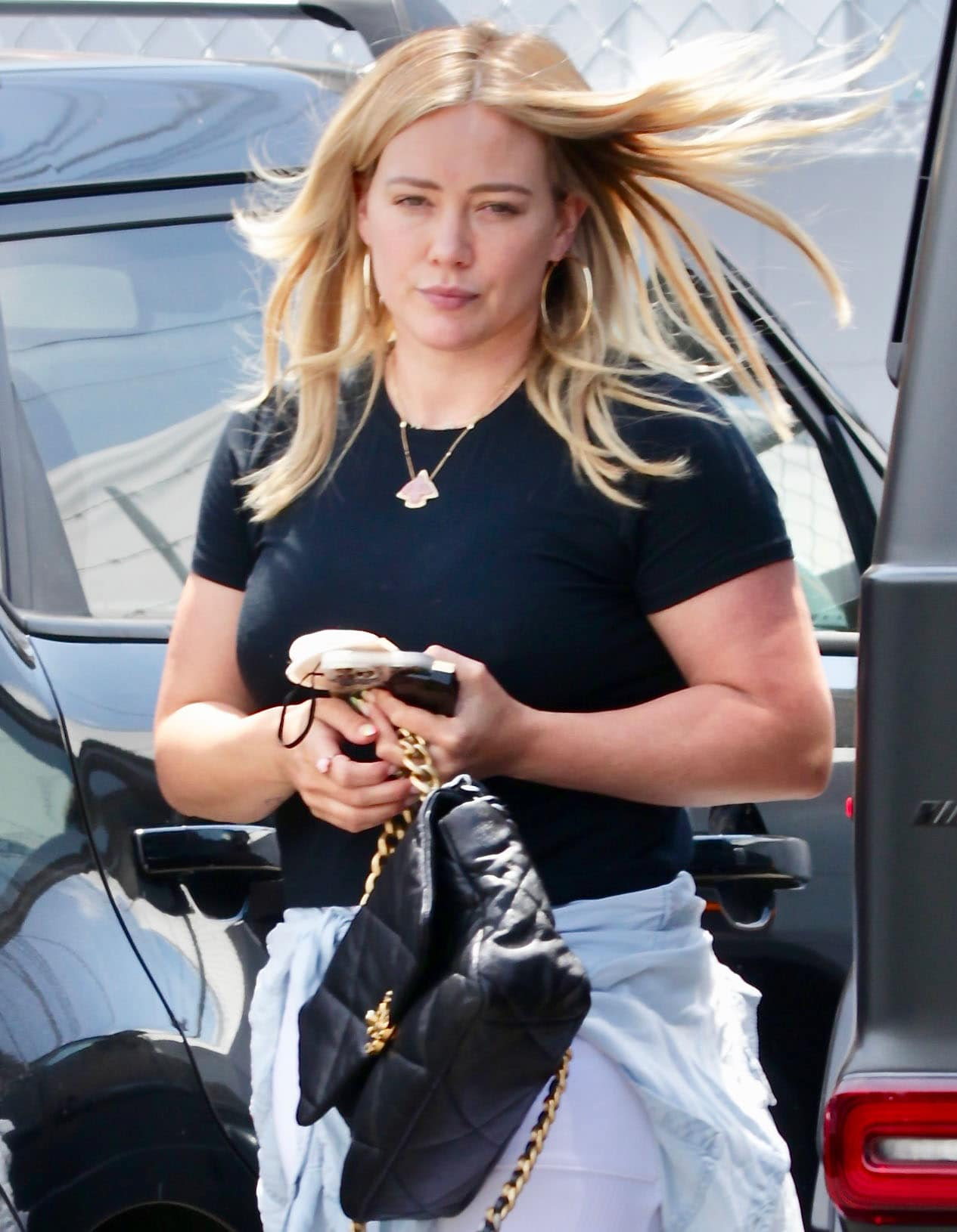 Hilary Duff styles her workout look with hoop earrings, a gold necklace, and a Chanel bag