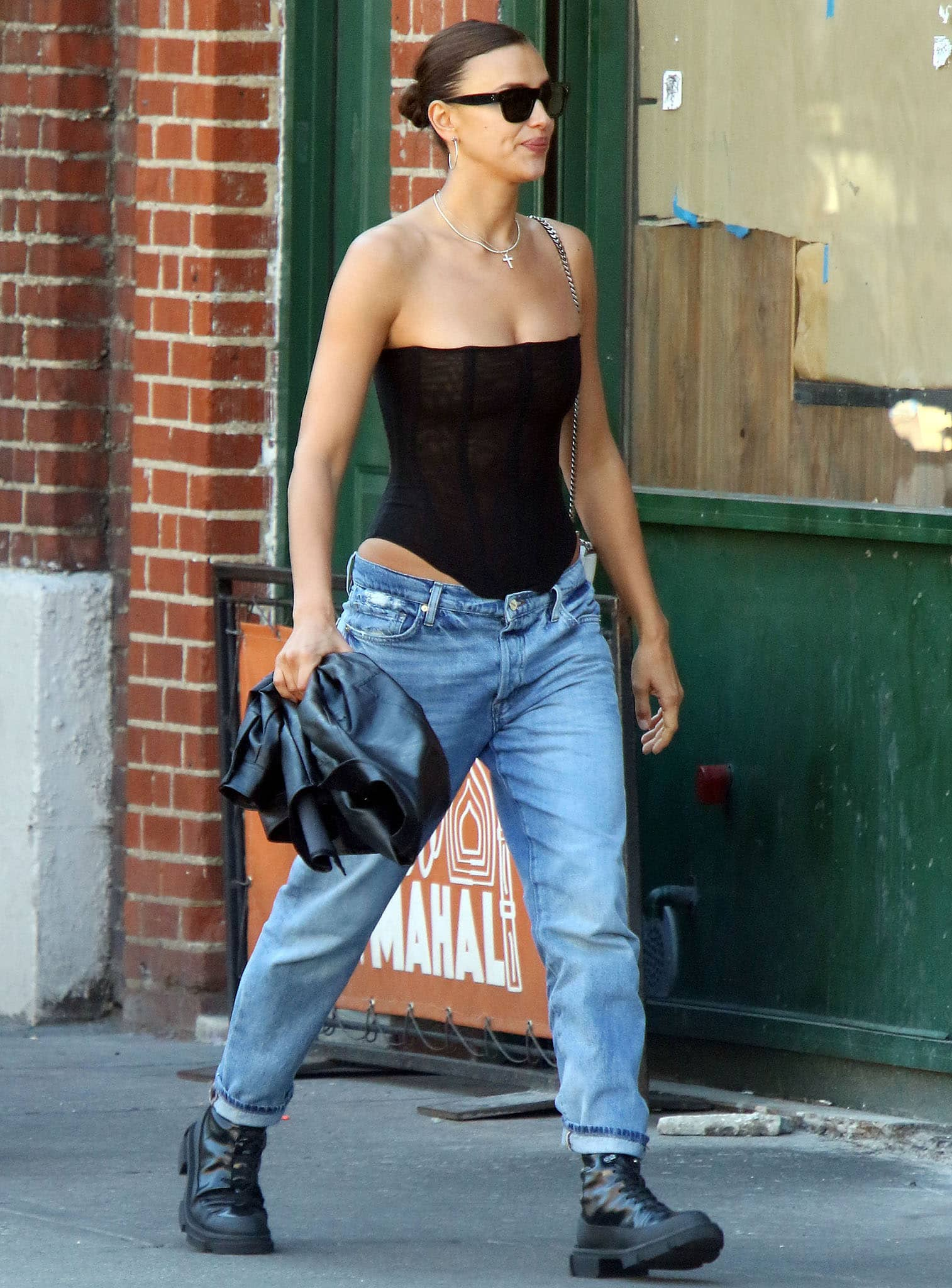 Irina Shayk embraces the whale tail trend in a black naked corset from Are You Am I paired with low-rise jeans
