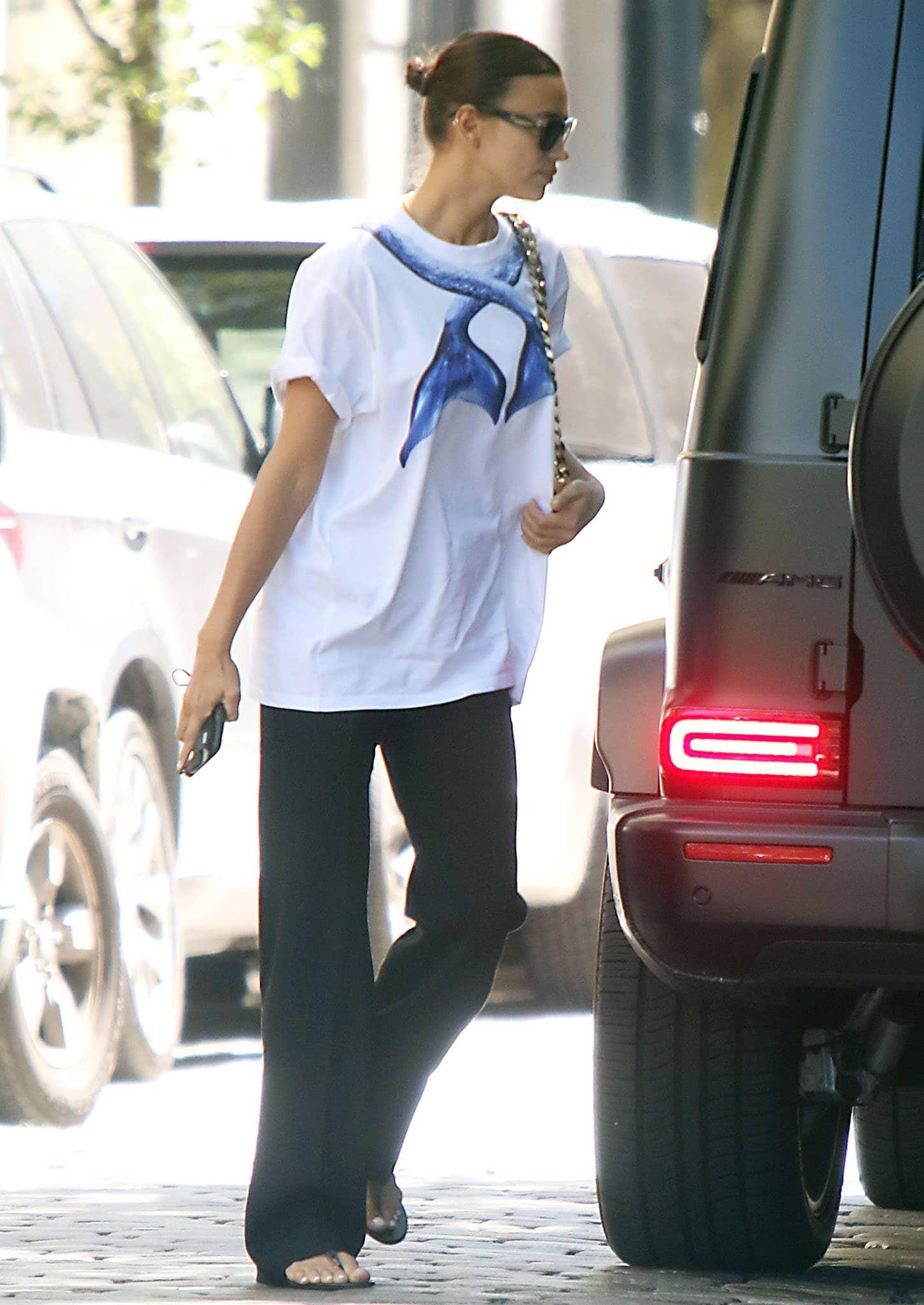 Irina Shayk keeps things casual in Burberry mermaid tail-print white tee and black pants