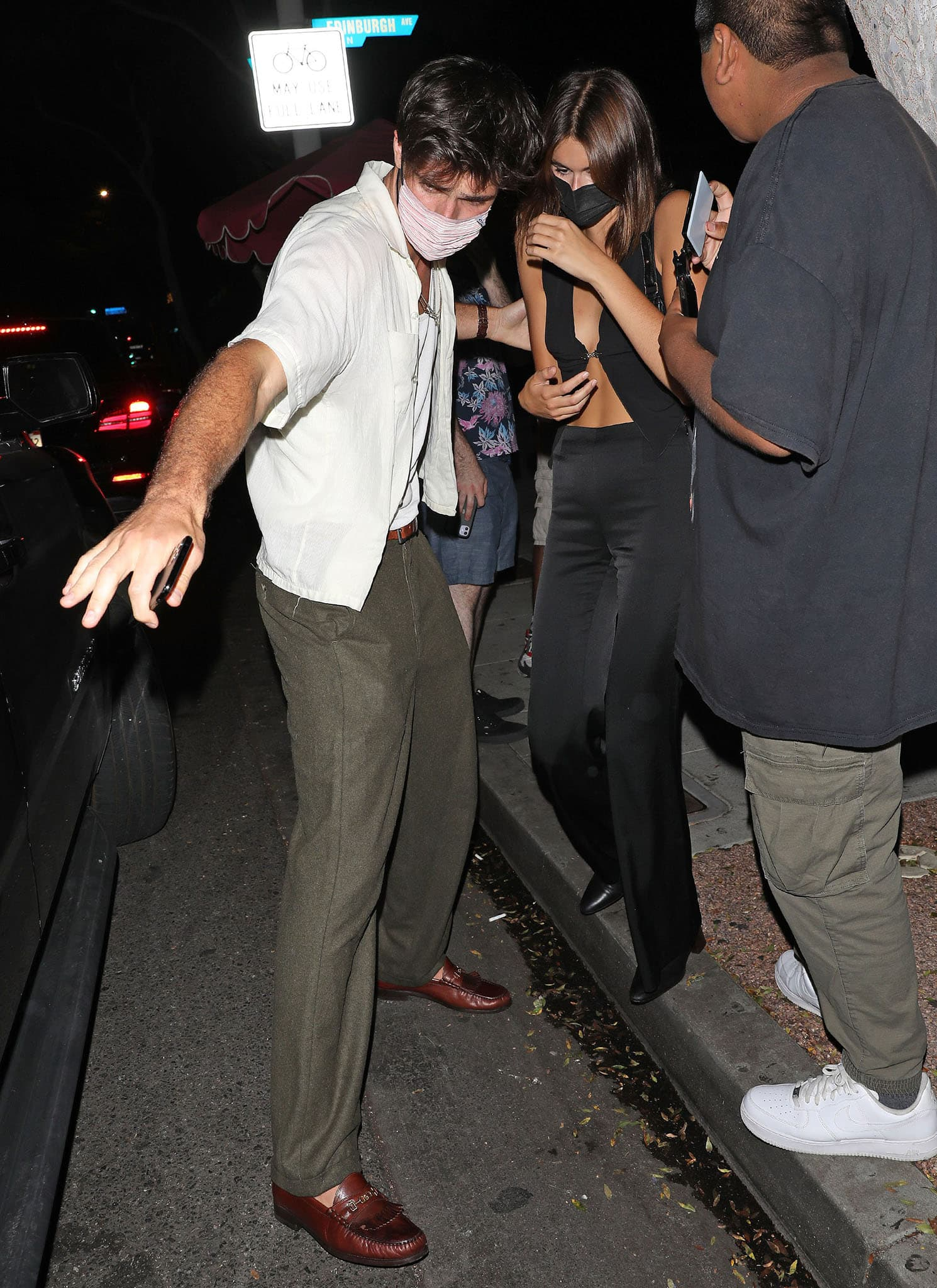 Jacob Elordi shields Kaia from the paparazzi in a cream shirt with khaki green pants and brown loafers