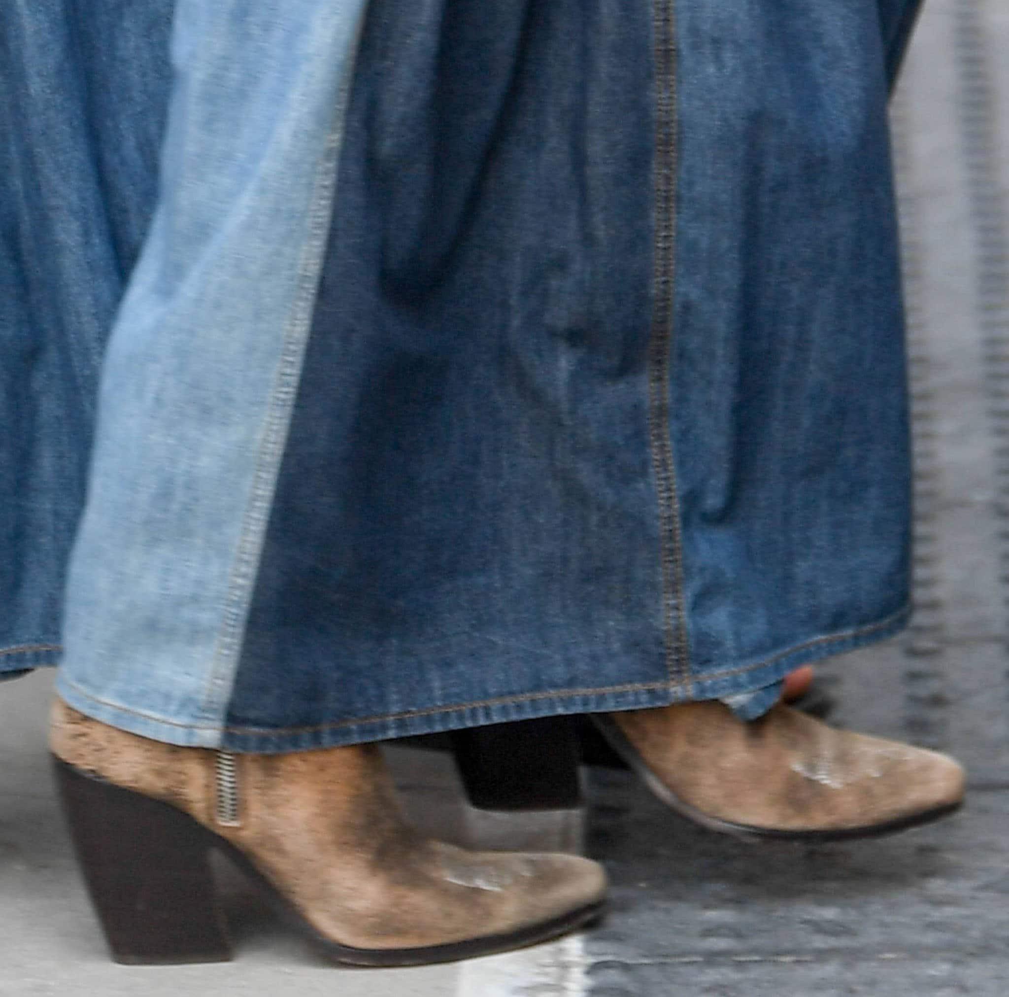 Jennifer Lopez teams her denim maxi skirt with Ralph Lauren distressed cowboy boots