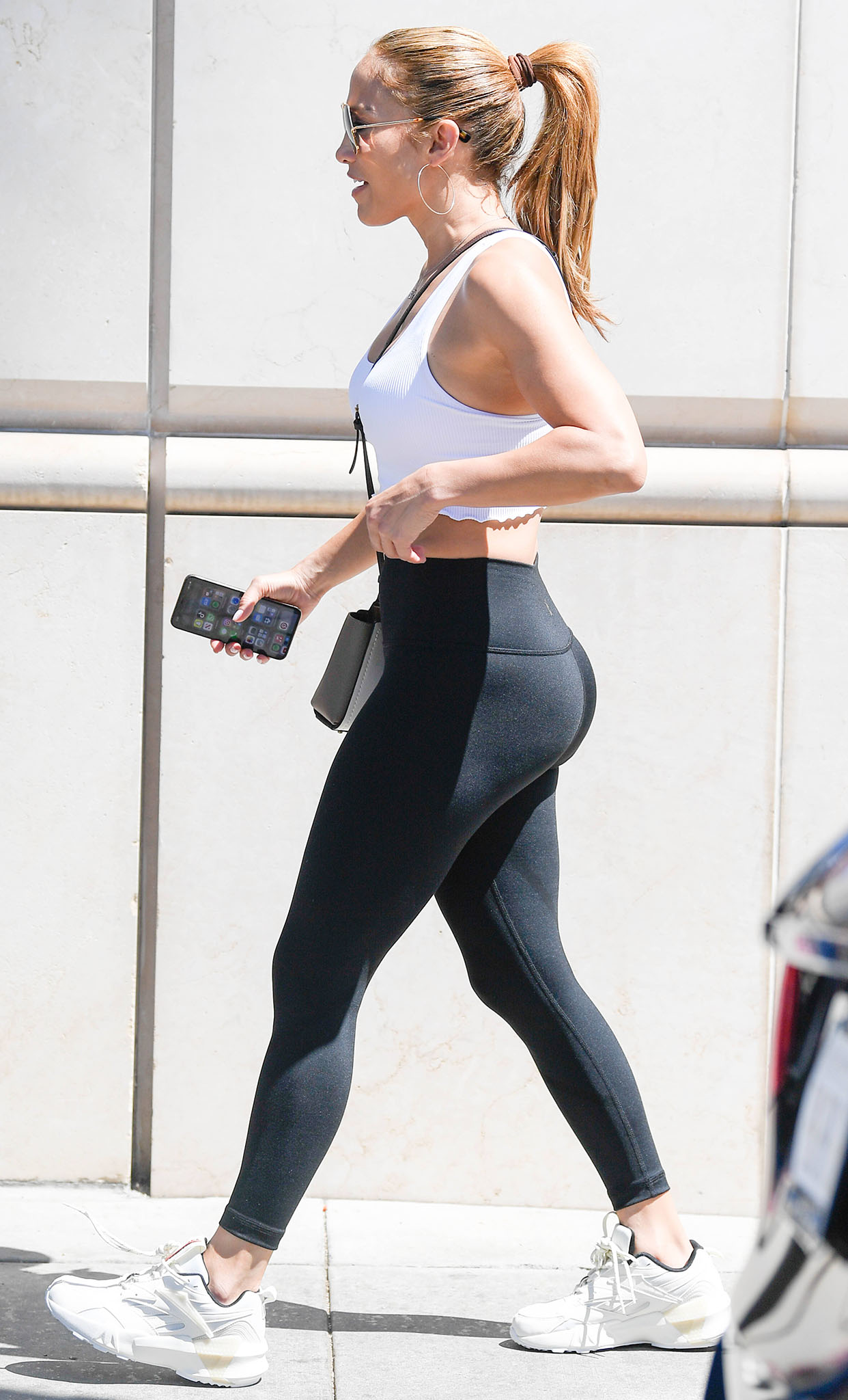 Jennifer Lopez pairs a white cropped tank top with Style Reform high-waisted black leggings