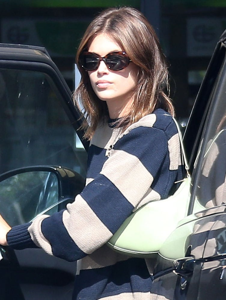 Kaia Gerber carries a sage green Celine Ava bag and hides her eyes behind a pair of Celine Triomphe sunglasses