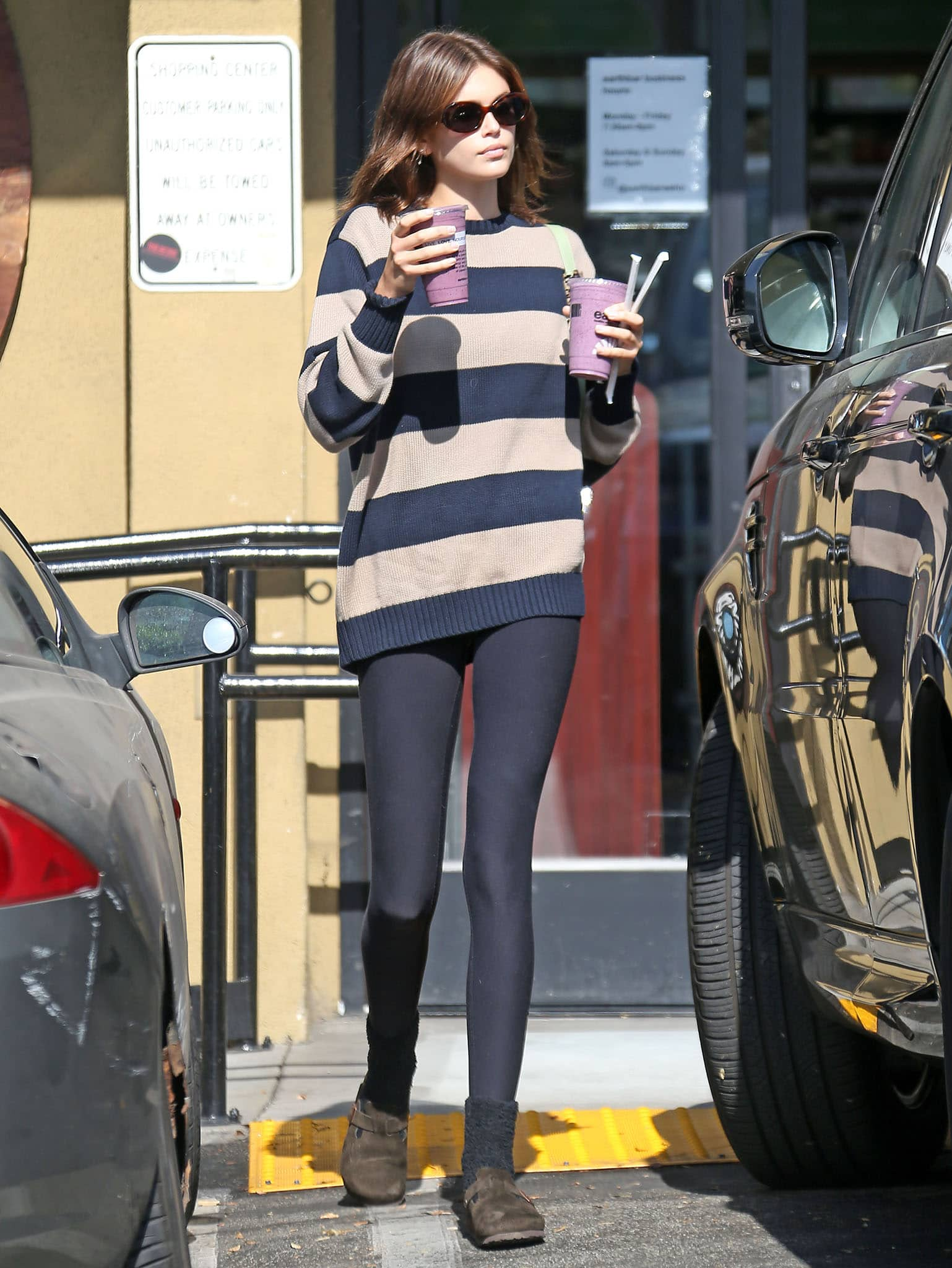 Kaia Gerber grabs smoothie in a striped sweater with black leggings at Earth Bar in Los Angeles on June 22, 2021