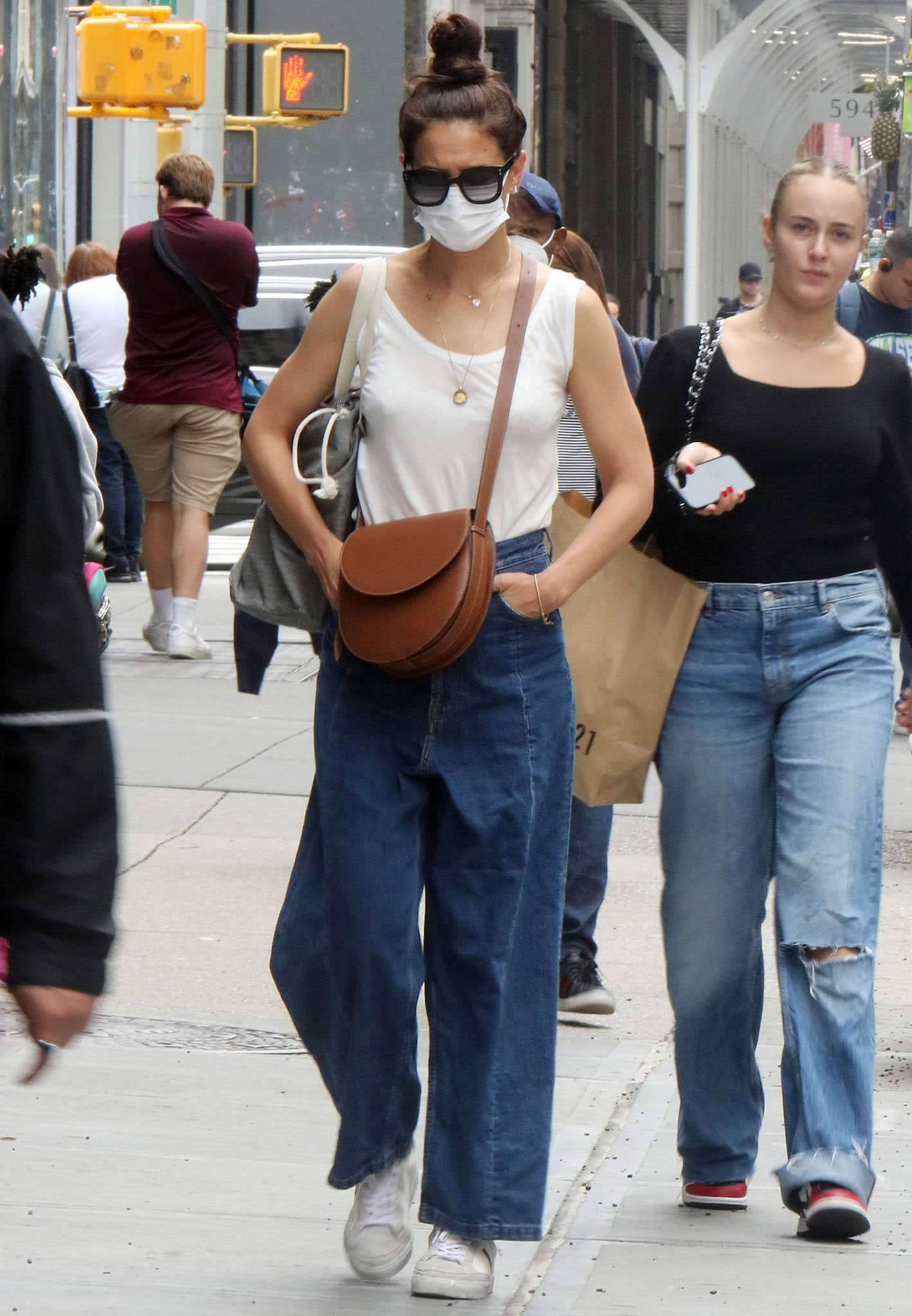 Katie Holmes' summer outfit includes an off-white tank top and a pair of baggy denim jeans