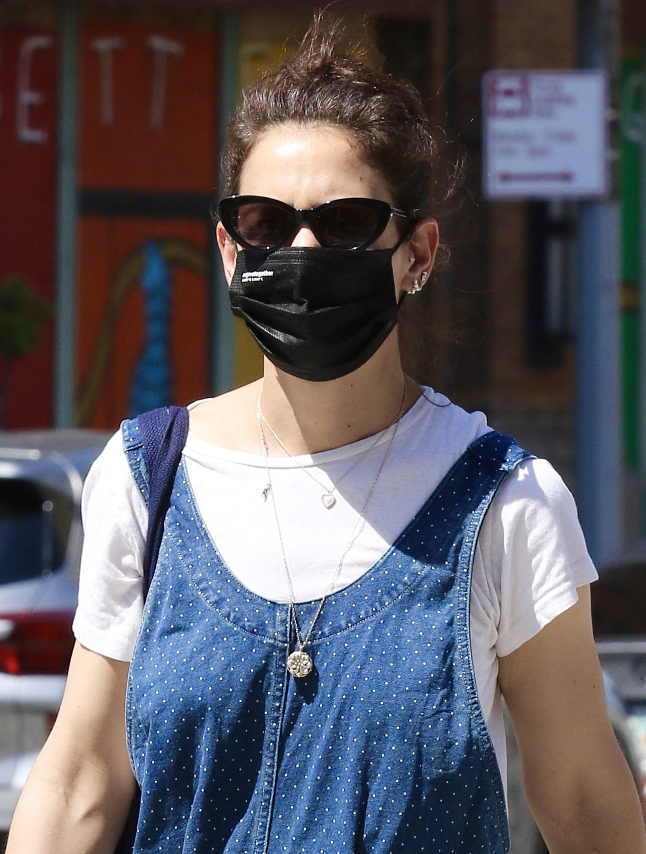 Katie Holmes pulls her naturally wavy tresses up into a messy bun and shields her eyes behind a pair of cat-eye sunglasses