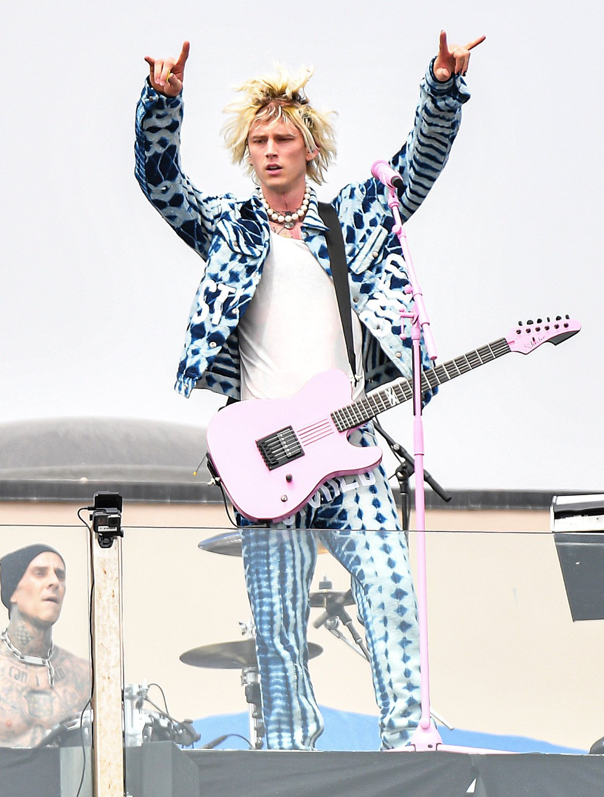 Machine Gun Kelly wears blue and white tie-dye-style jacket and matching pants