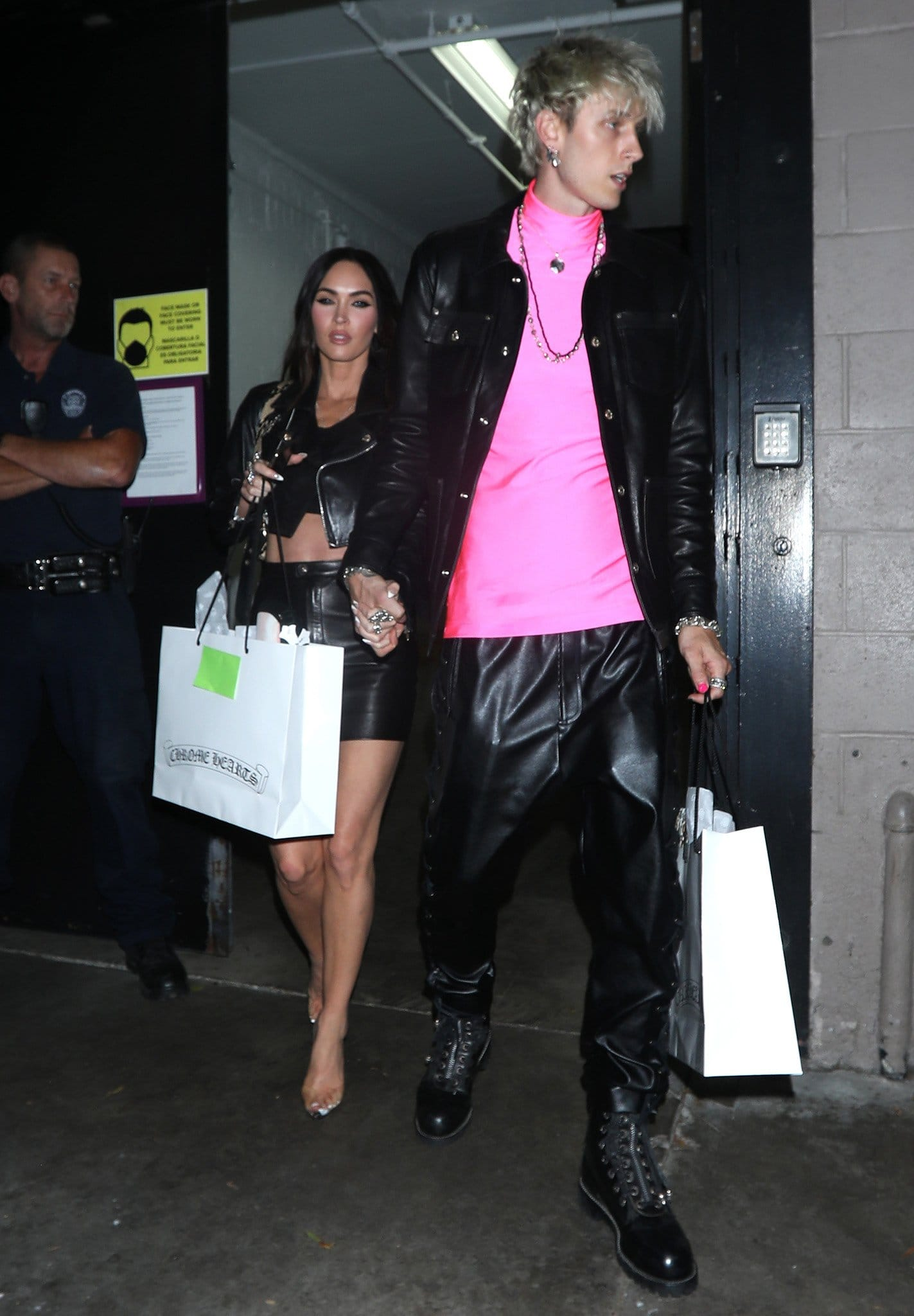 Machine Gun Kelly draws attention in his neon pink top with leather pants and jacket