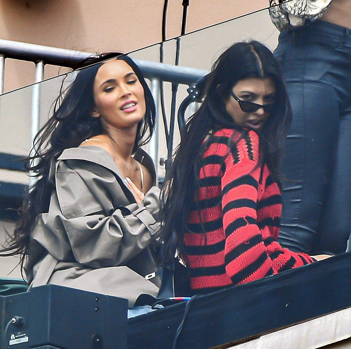 Kourtney Kardashian teams her red and black Raf Simons sweater with Prada chunky boots