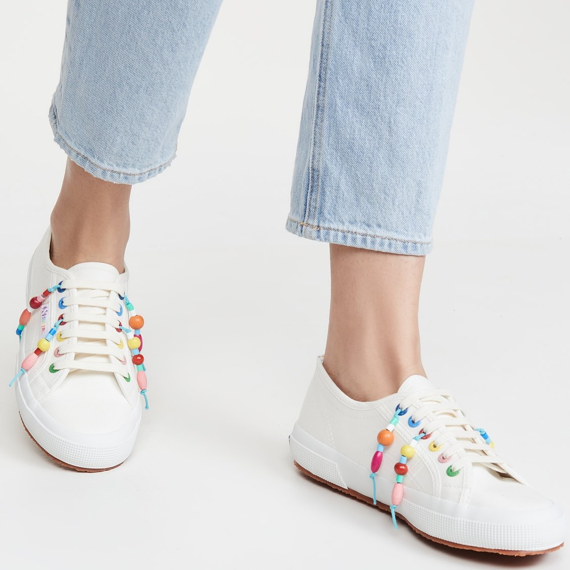 Off white Mira Mikati x Superga sneakers with multicolored grommets and beaded tassels for a carefree off-duty look