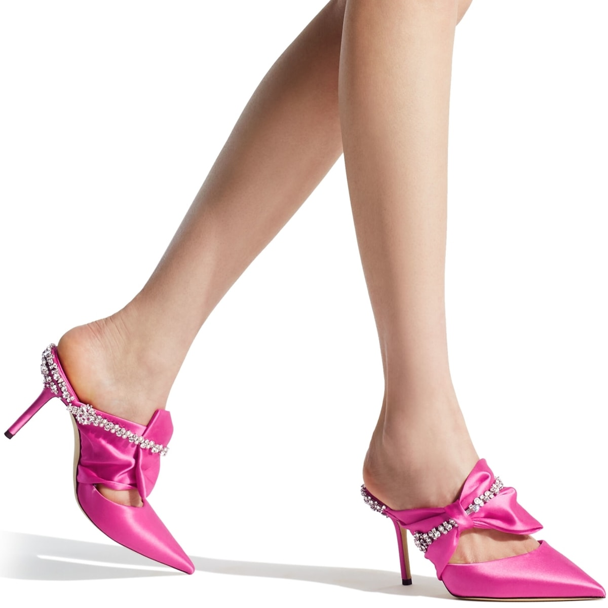 These pink satin Nina mules feature an elegant pleated bow accented by an embroidered chain of crystals