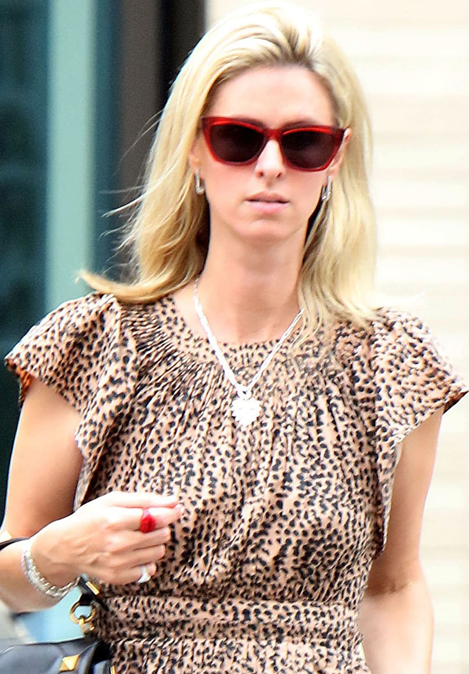 Nicky Hilton styles her look with red-framed sunglasses, minimal makeup, and loose tresses