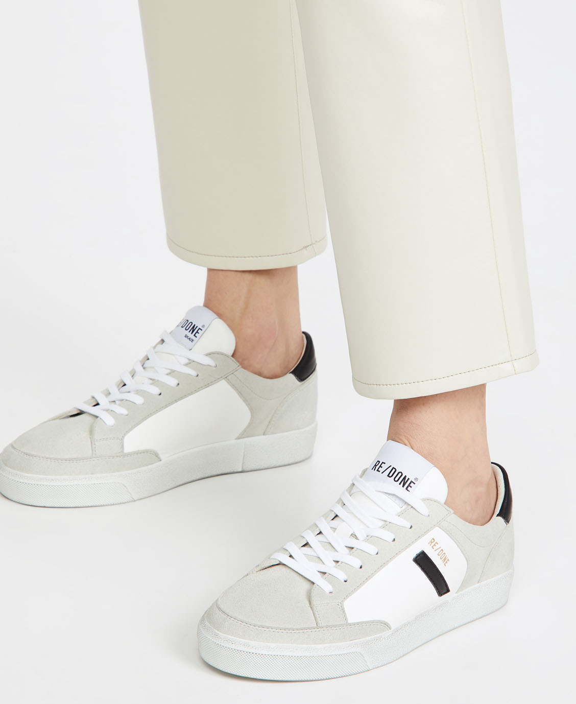 A pair of sustainable sneakers featuring a subtle mix of faux leather and faux suede materials