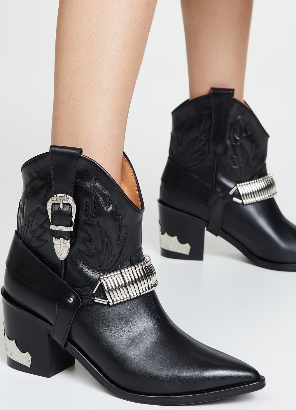A boldly modern take on a classic cowboy boot, these black buckled booties add a harness strap and eye-catching hardware to a must-have Western style