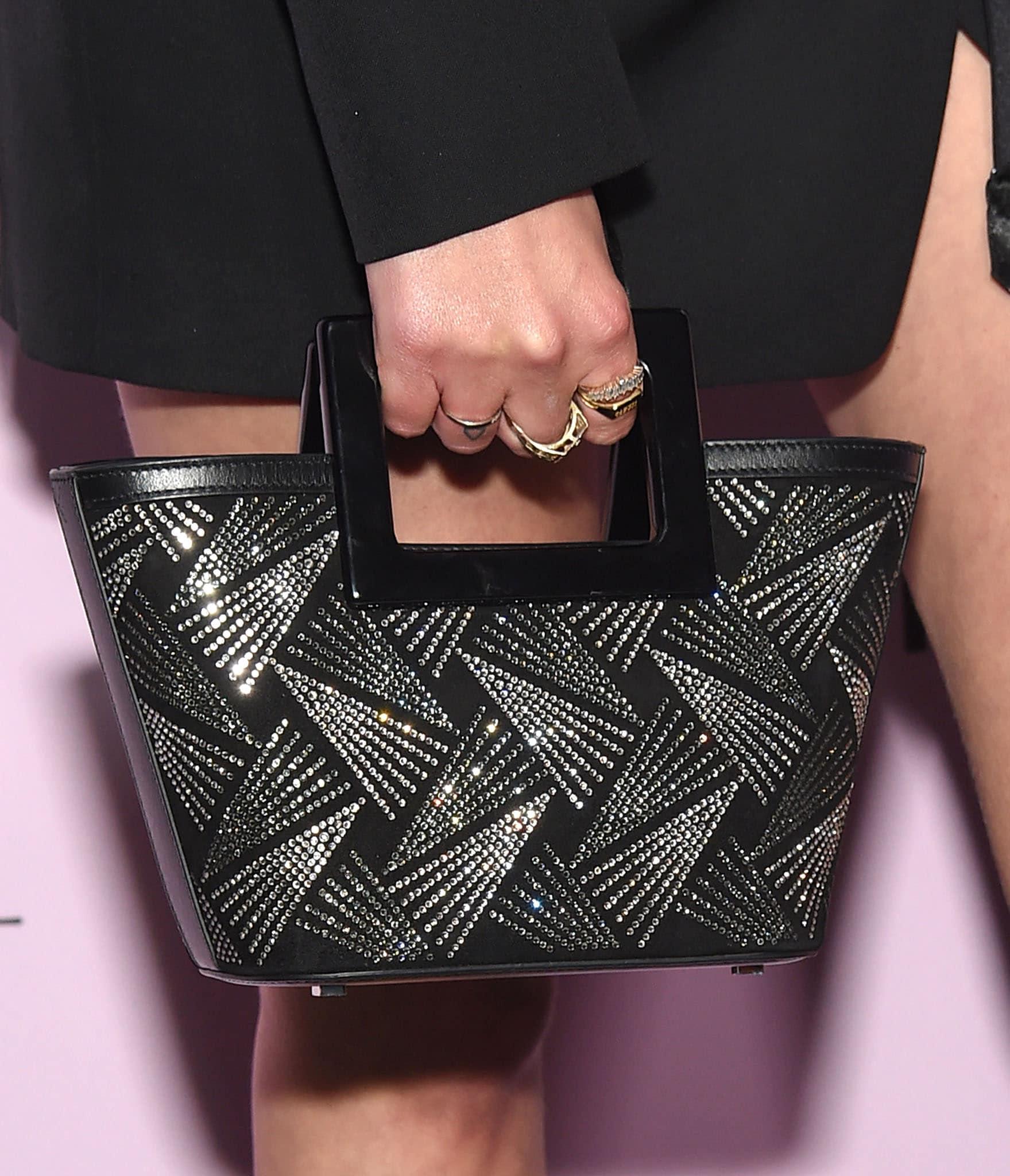 Ashley Benson carries the fireworks-patterned Swarovski Micro Riviera bag from Marina Raphael