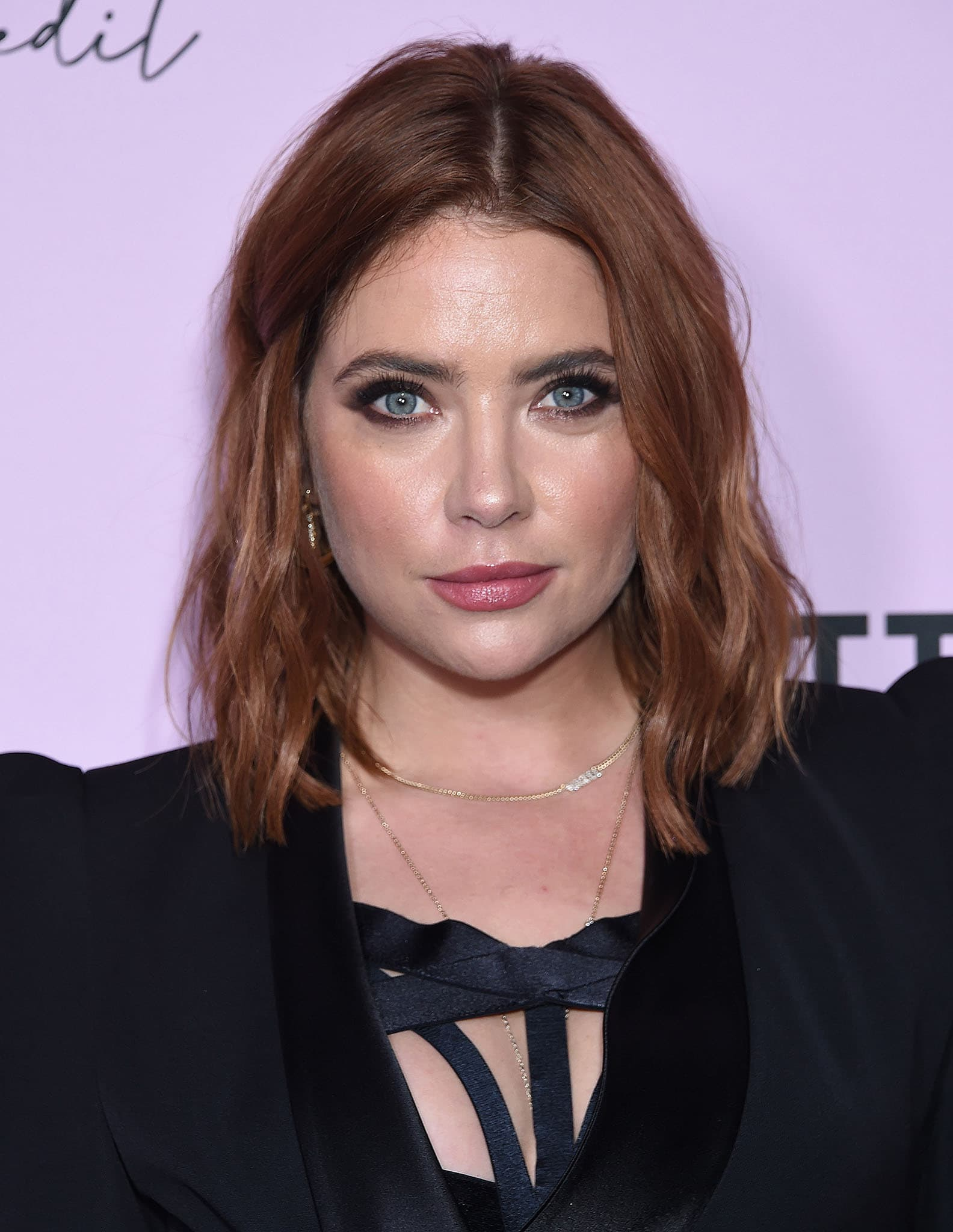 Ashley Benson wears her red hair in tousled waves with kohl-rimmed eyes and pink lipstick