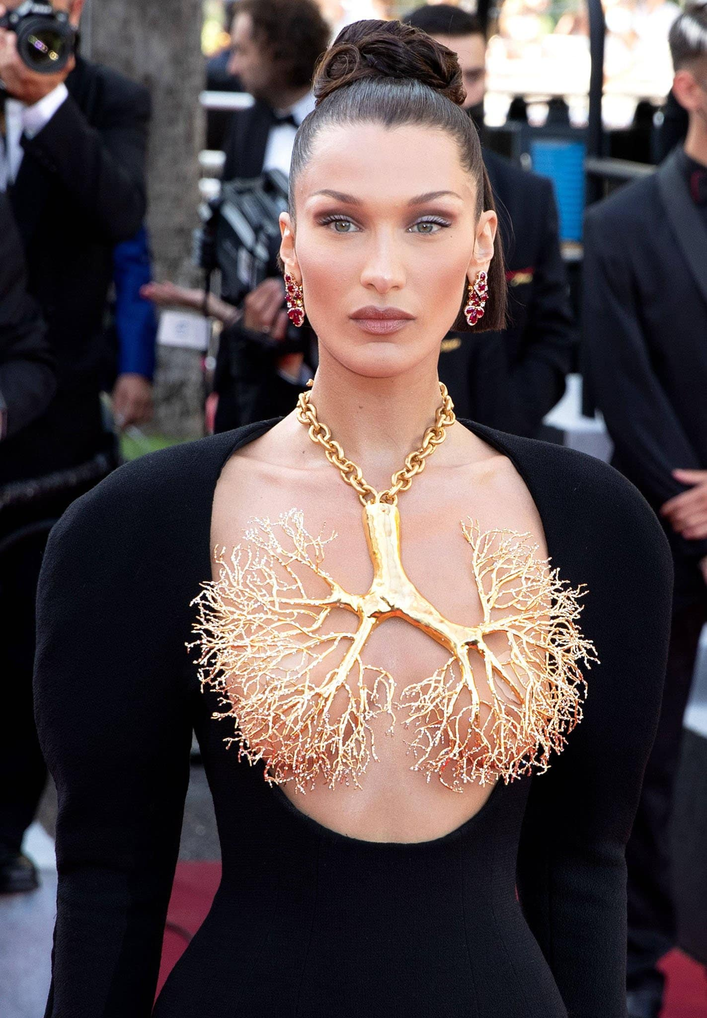 Wearing a gilded brass necklace of a human lung's pulmonary veins, Bella Hadid styles her tresses in an intricate updo and wears smokey eyeshadow with nude lipstick